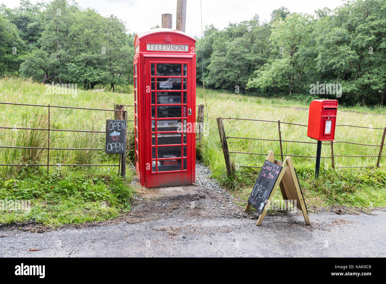 Telephone Red Box uses to sell cakes. Self service cakes in a Red Call Box in Cladich, Argyll, Scotland - Stock Image