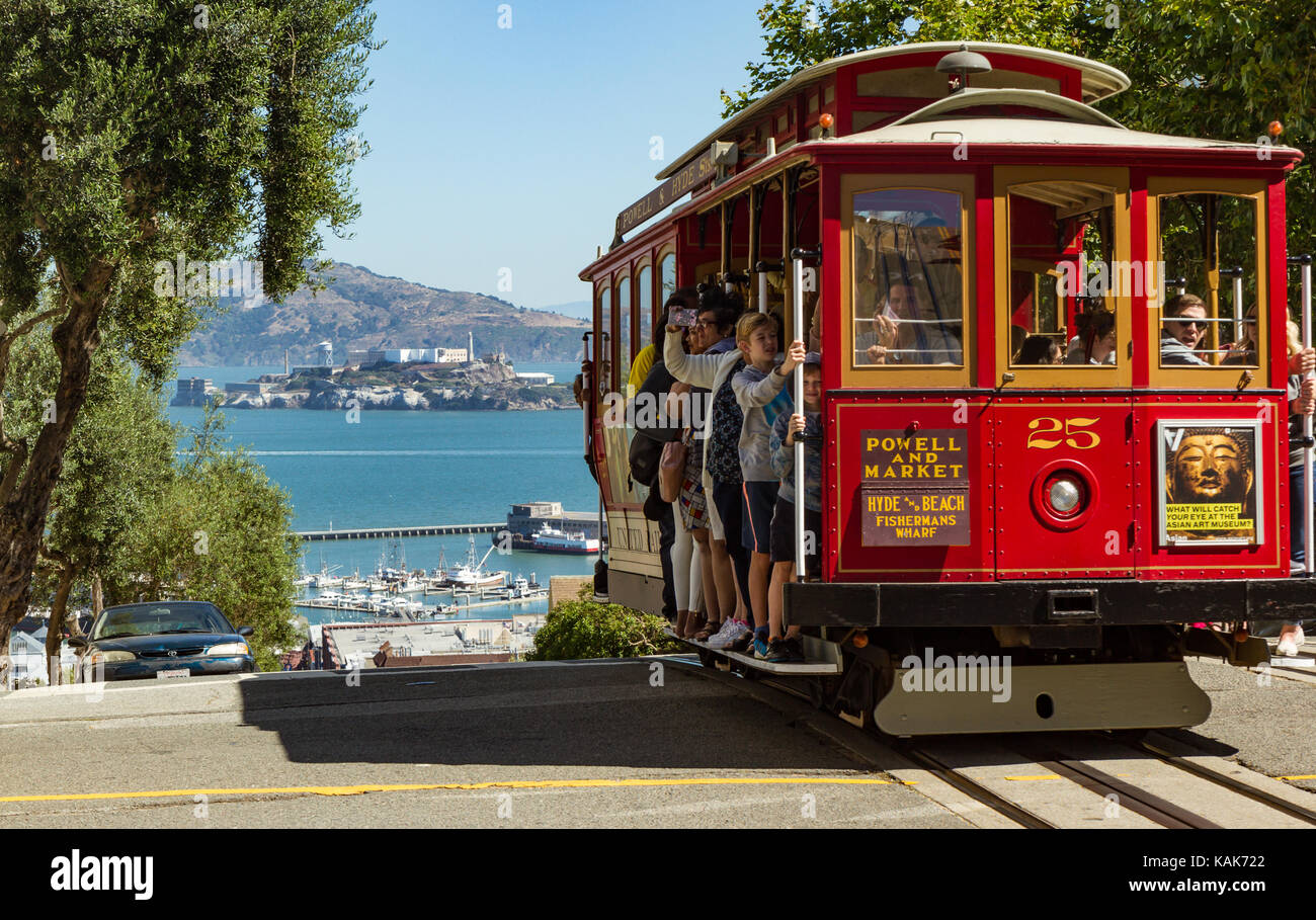Cable Car about to descend hill towards Alcatraz Island in San Francisco, California, USA. People riding in cable - Stock Image