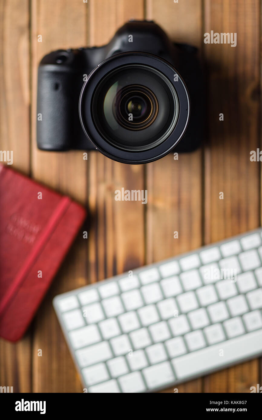 Professional digital camera and computer keyboard on wooden table. - Stock Image