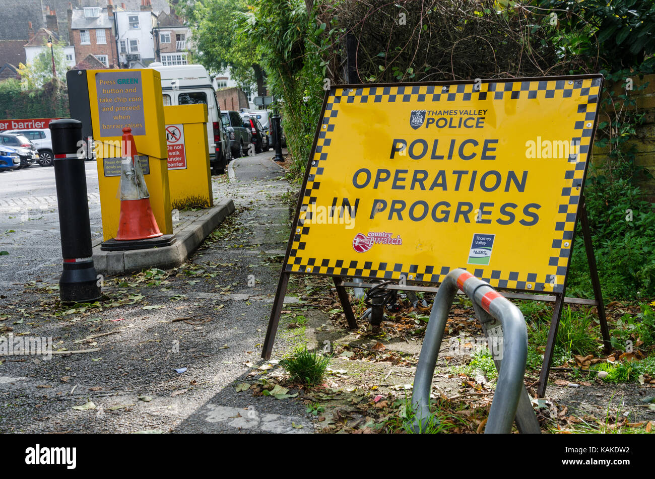 A yellow sign at the entrance to a car park in Windsor indicating that there is a police operation in progress. - Stock Image