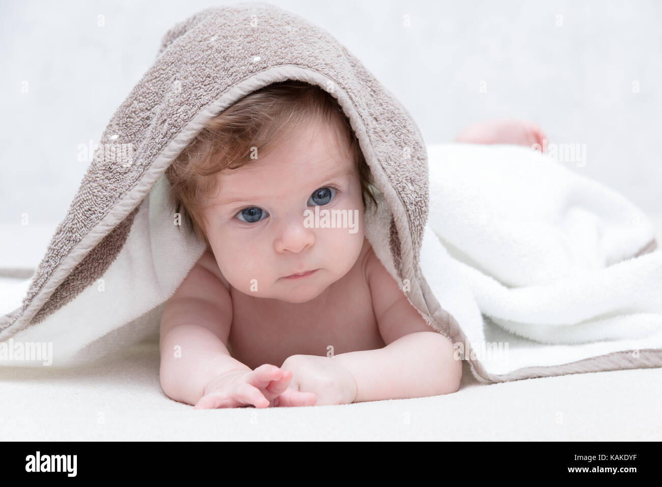 Cute newborn baby girl with beautiful blue eyes on a white terry coverlet adorable baby looking out under a white blanket or towel