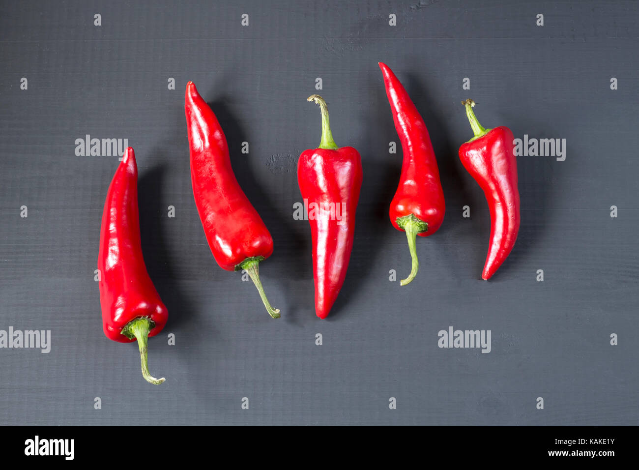 cayenne chilli peppers on wooden background - Stock Image