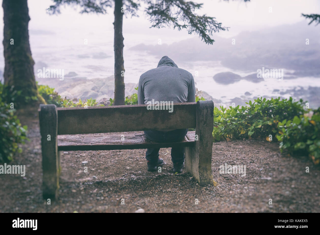 Sad and lonely man sitting on bench overlooking sea on Vancouver Island - Stock Image