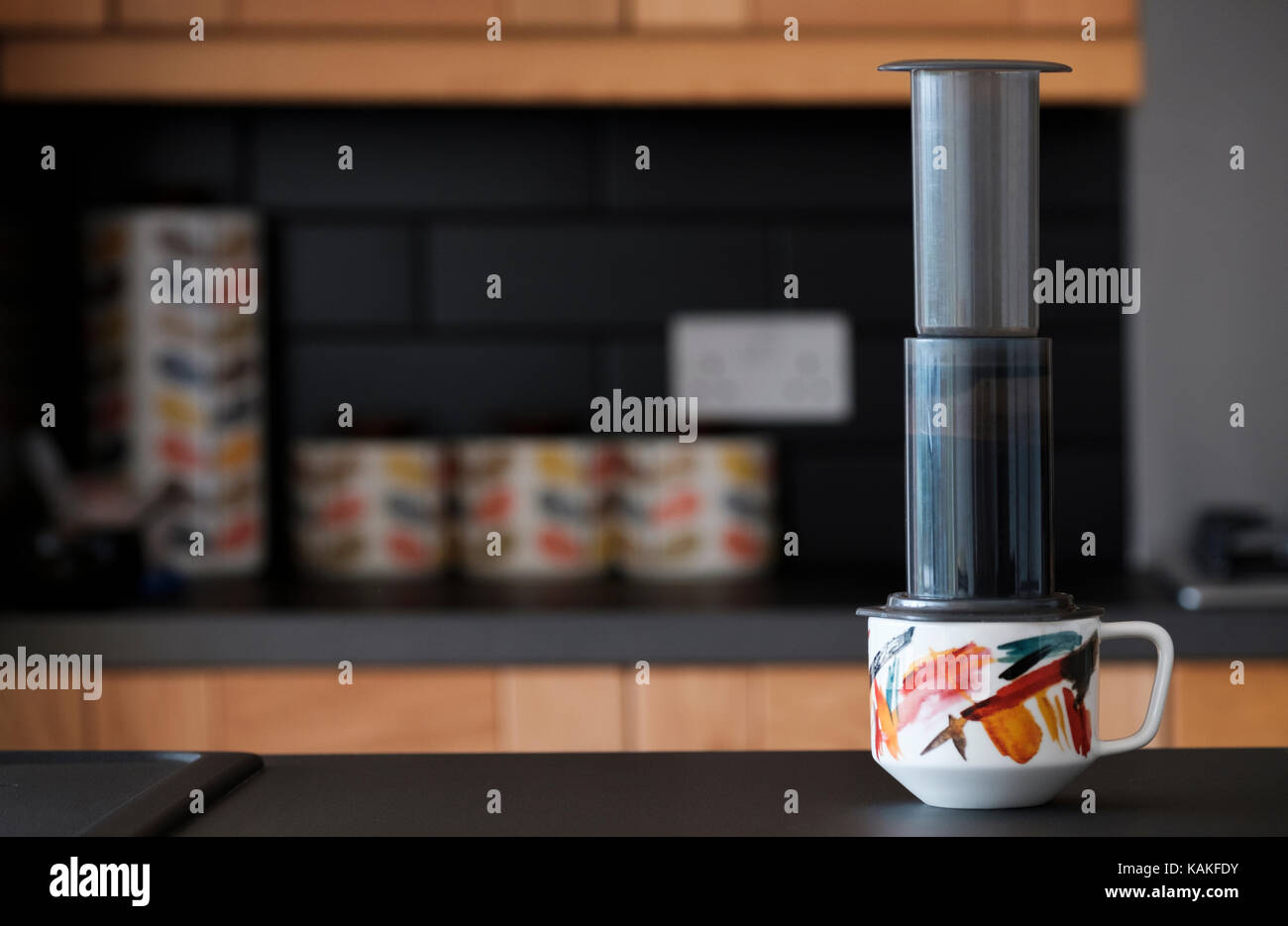 An aeropress.inc coffee maker being used to brew coffee in a domestic kitchen - Stock Image