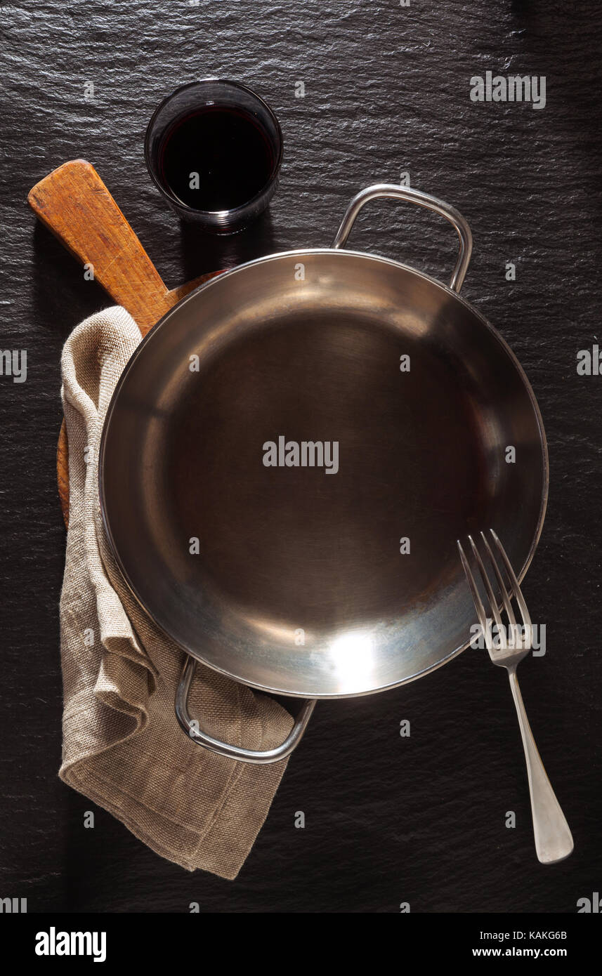 empty serving pan on Slate black stone background Stock Photo