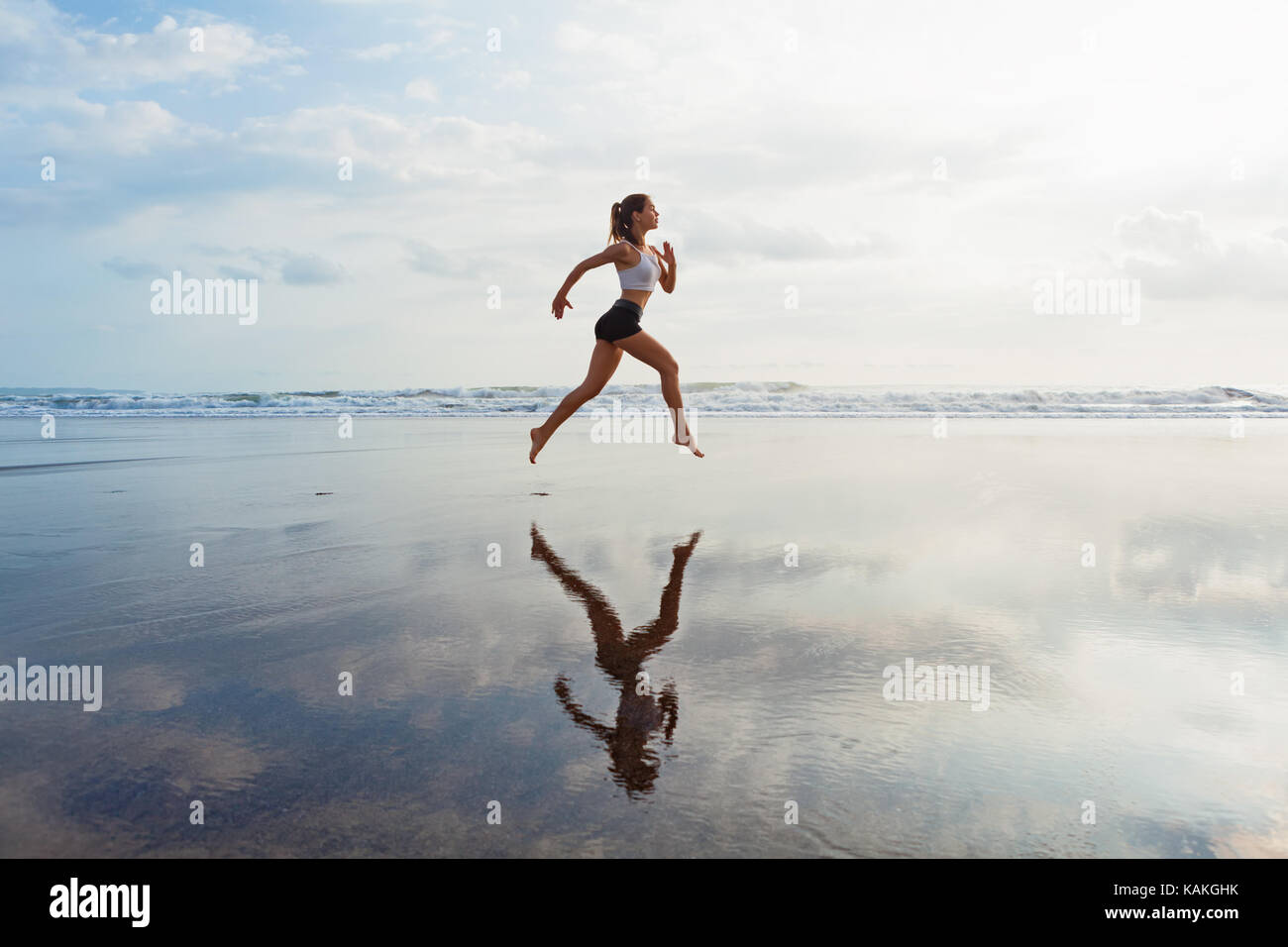 Barefoot sporty girl with slim body running along sea surf by water pool to keep fit, health. Beach background with - Stock Image