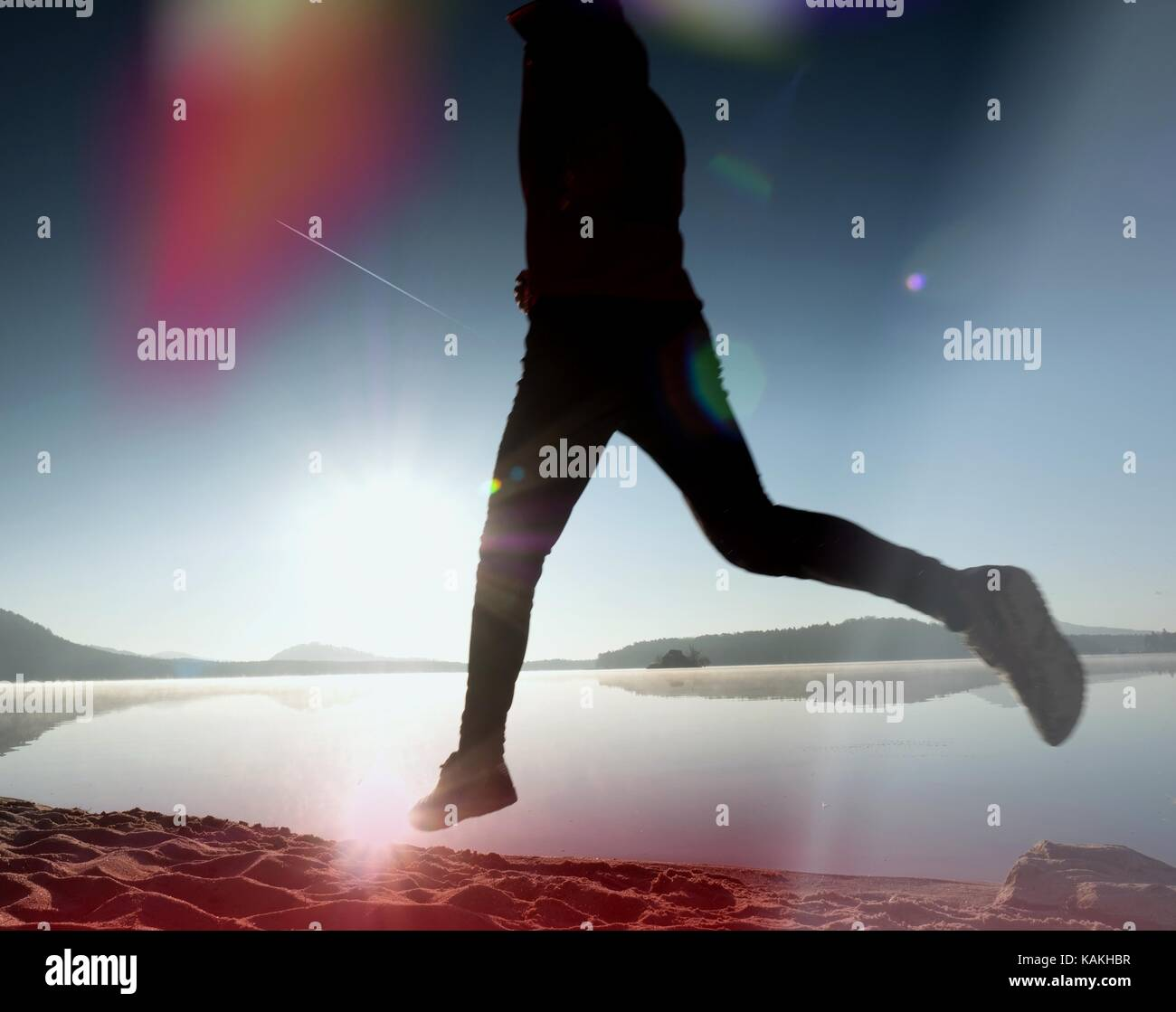 Leakage of light in the lens. Damaged photo effect. Handsome slim  man running on the beach. Exercising  silhouette - Stock Image