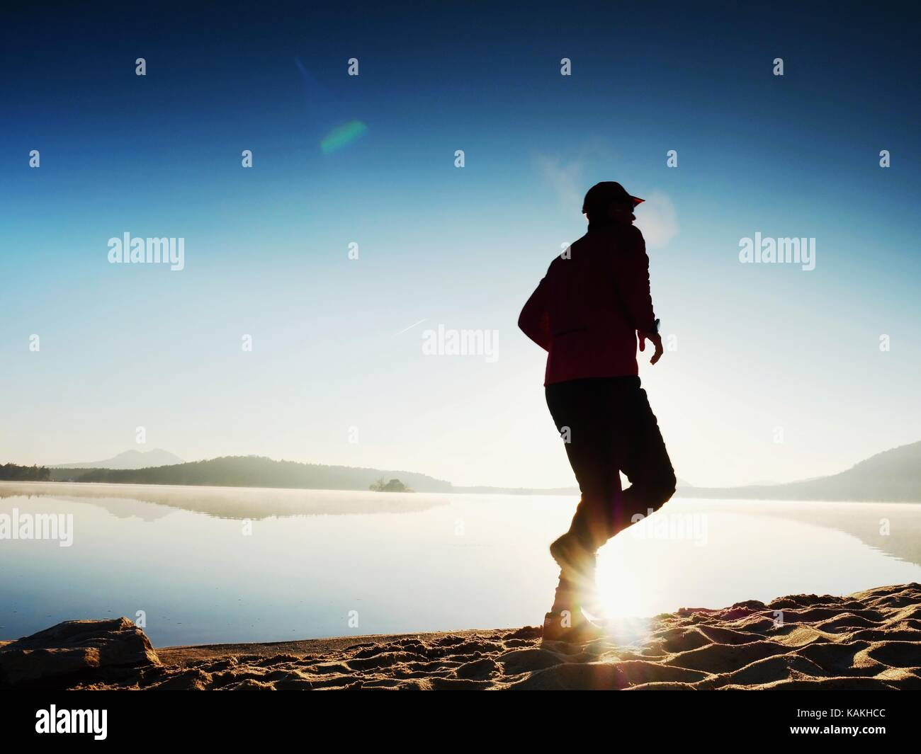 Running man. Boy quickly running on the morning beach. Sportsman runner, jogging guy during the sunrise above sandy - Stock Image