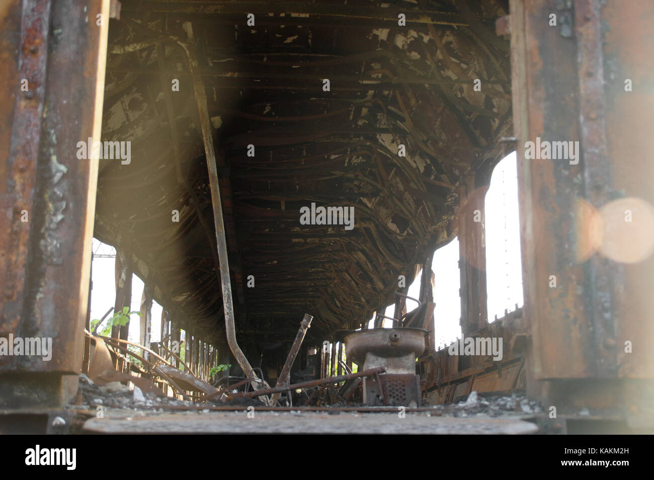 Rusty, burned and destroyed old railway wagon - Stock Image