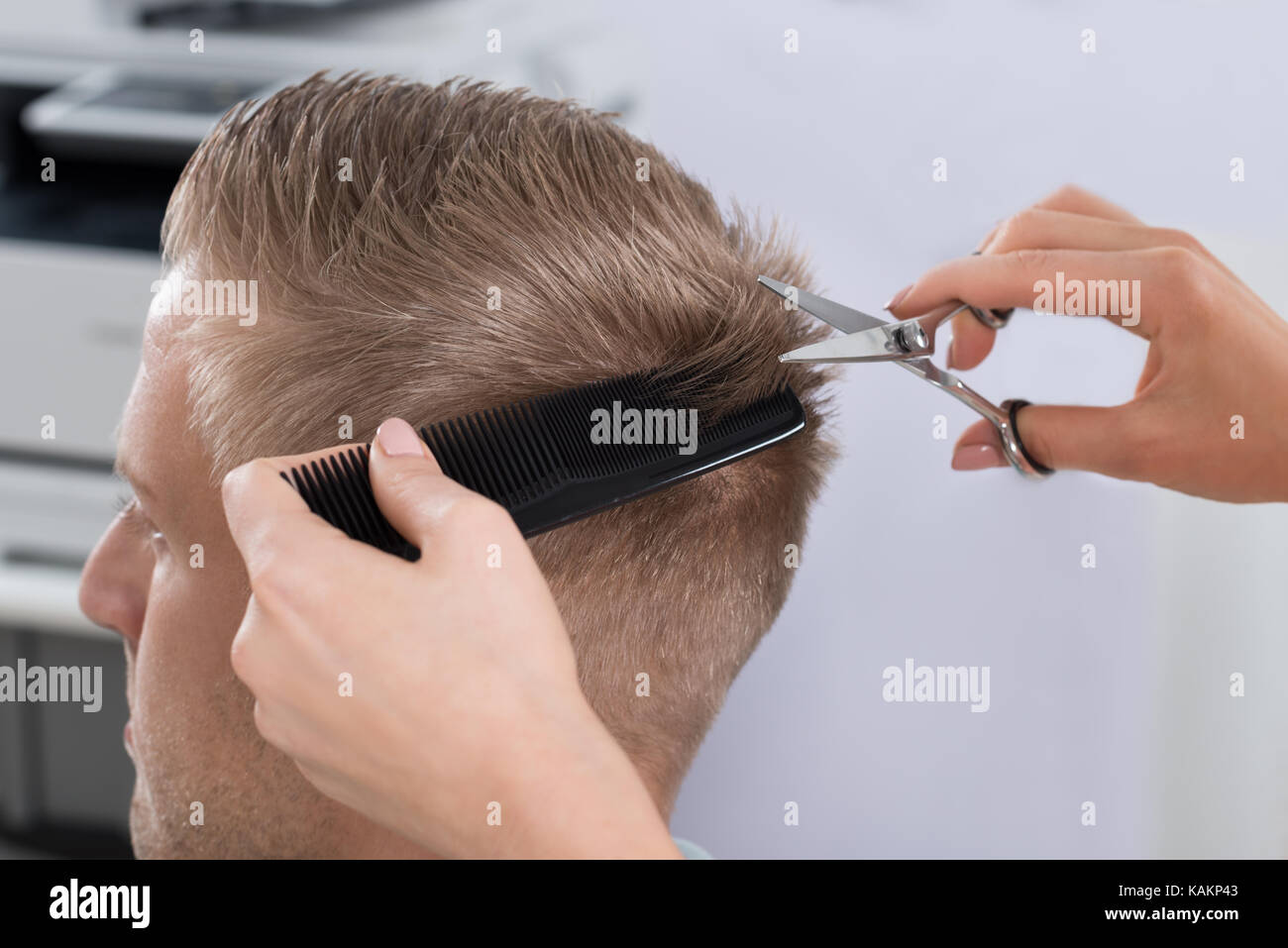 Young man getting haircut from female hairdresser at salon - Stock Image