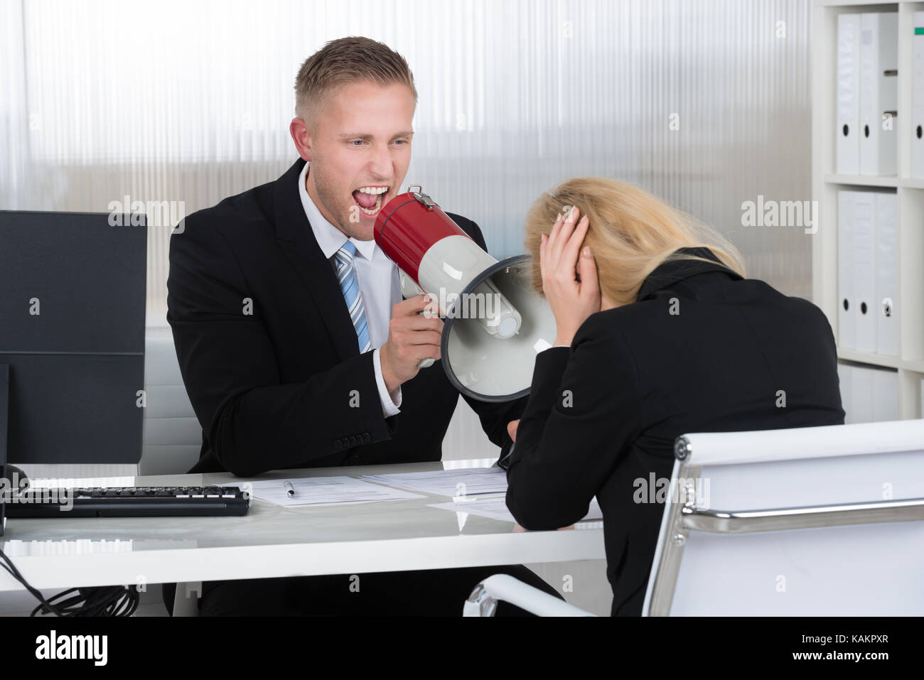 Boss shouting at businesswoman through loudspeaker at desk in office Stock Photo