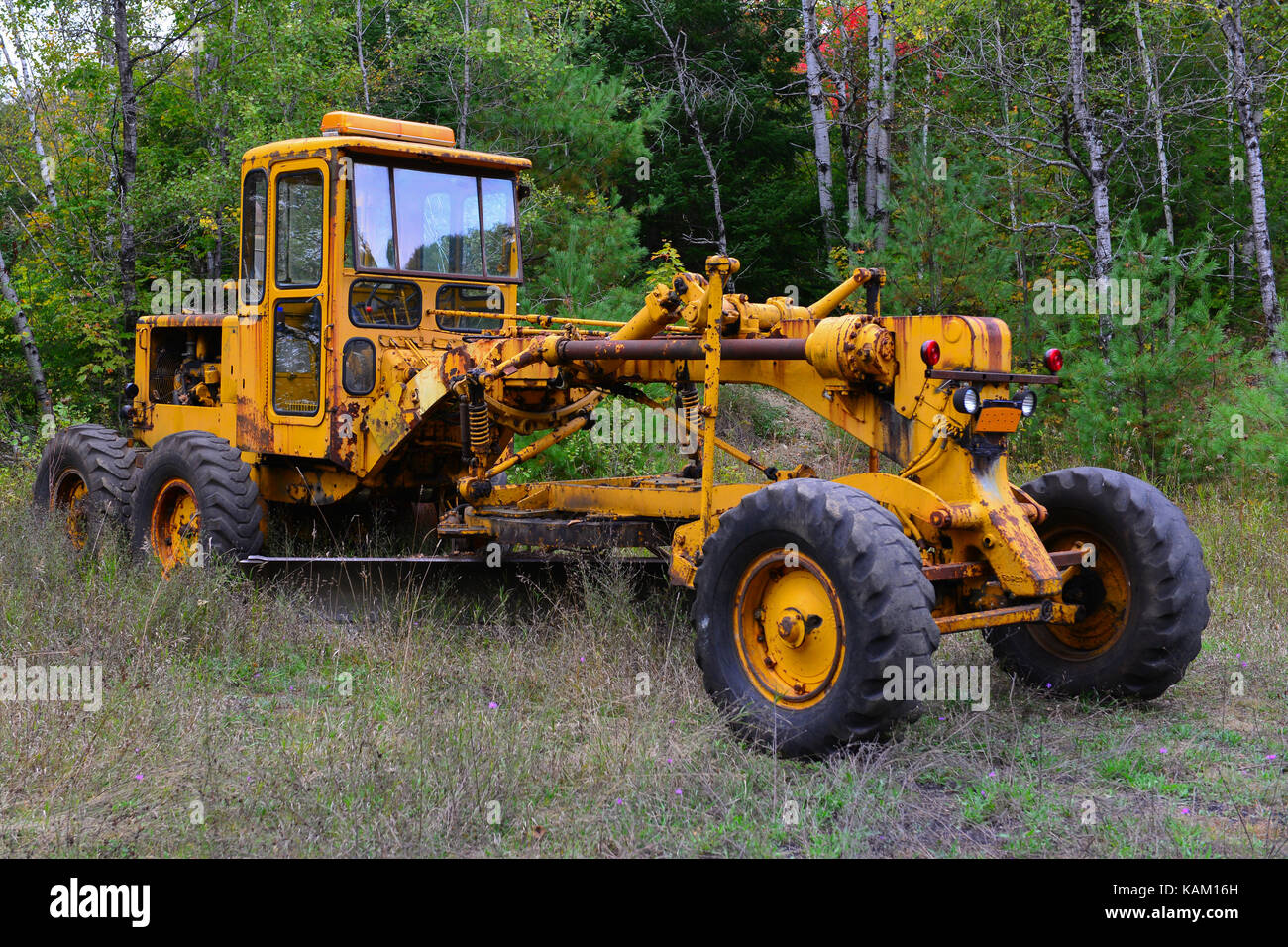 Rusty old road excavator grader parked in the Adirondack