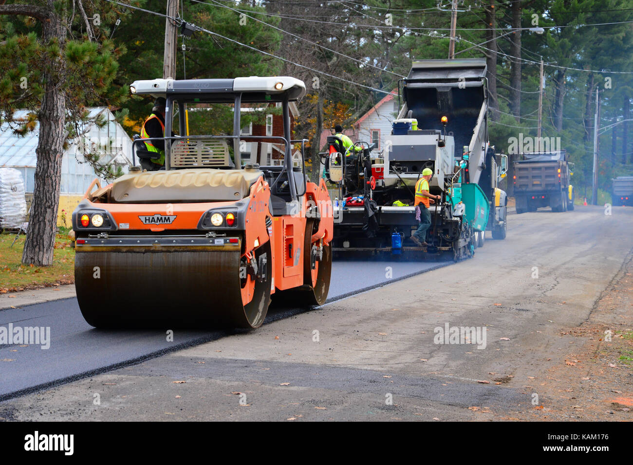 Road crew and equipment paving and rolling a village street. - Stock Image