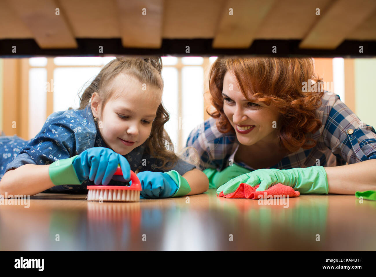 Mother and daughter do the cleaning in the house. Happy woman and little child girl wiped the floor. - Stock Image