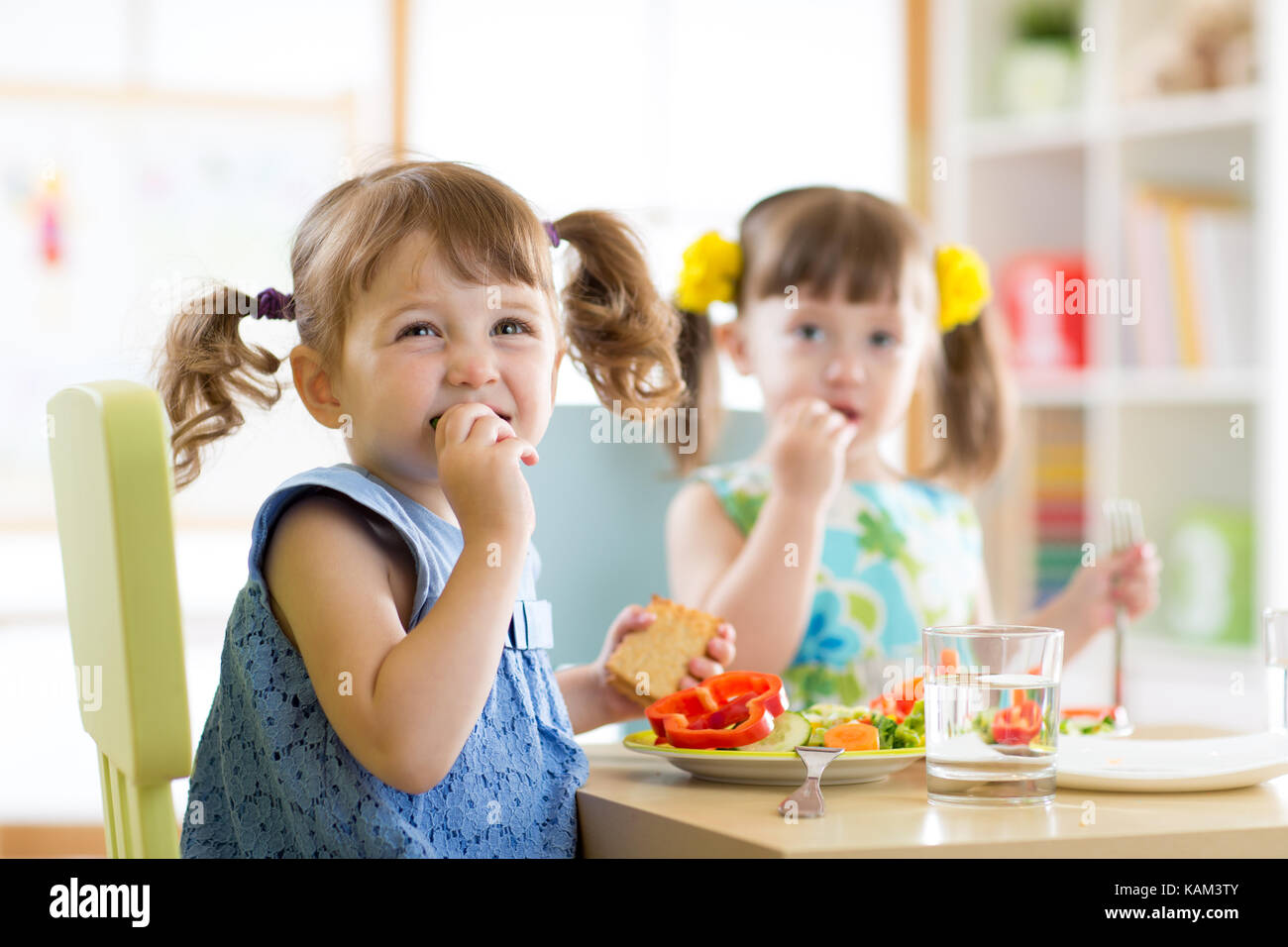 Cute little children eating food at daycare Stock Photo