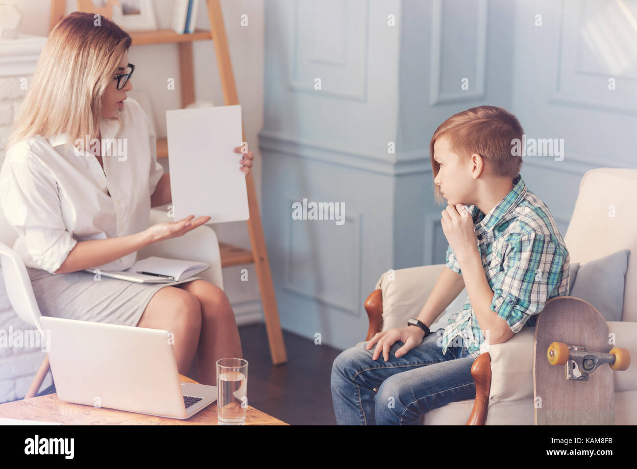 Professional psychologist having a test with a schoolboy - Stock Image