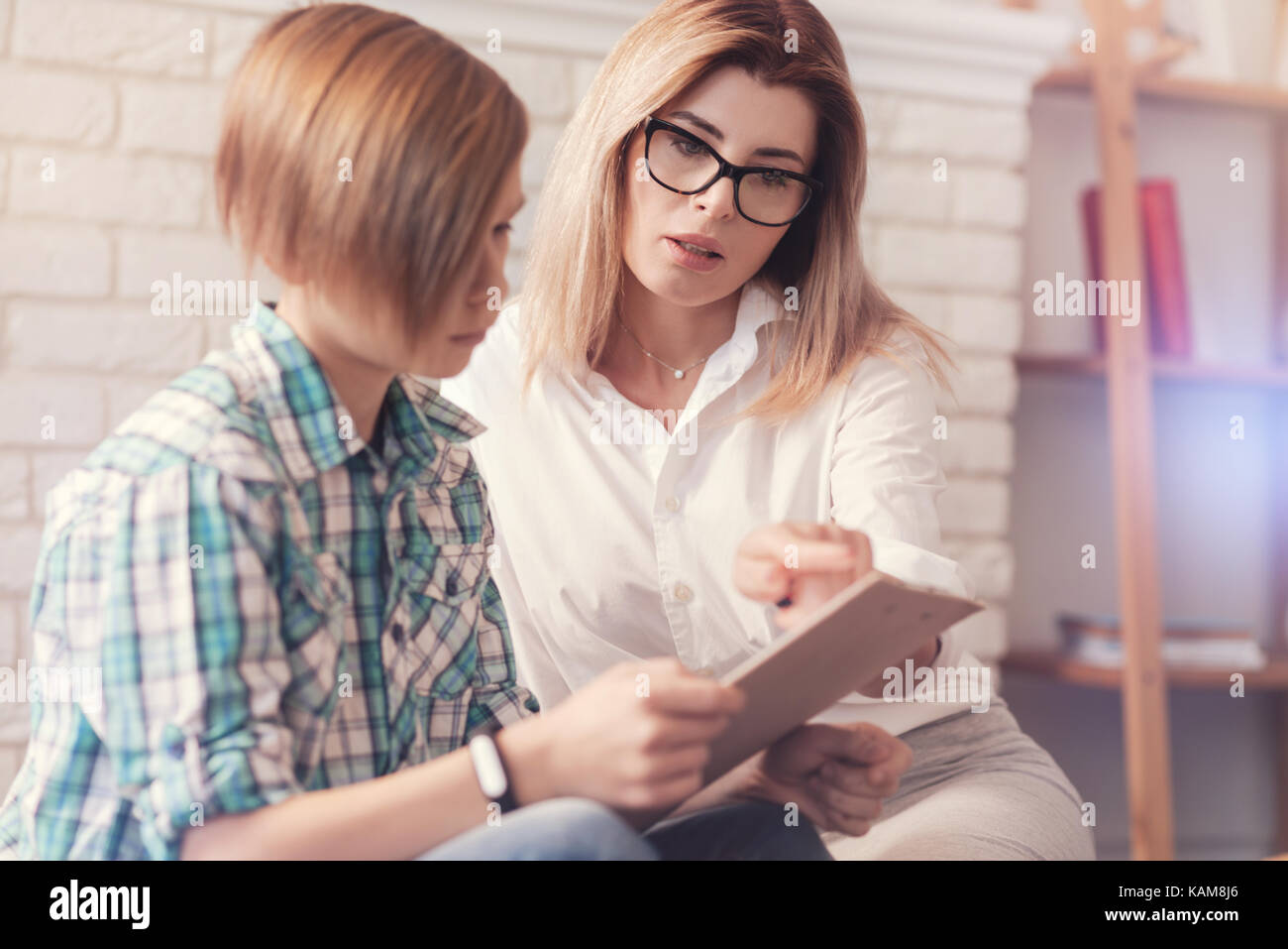 Professioanl female psychologist givign a test to a schoolboy - Stock Image