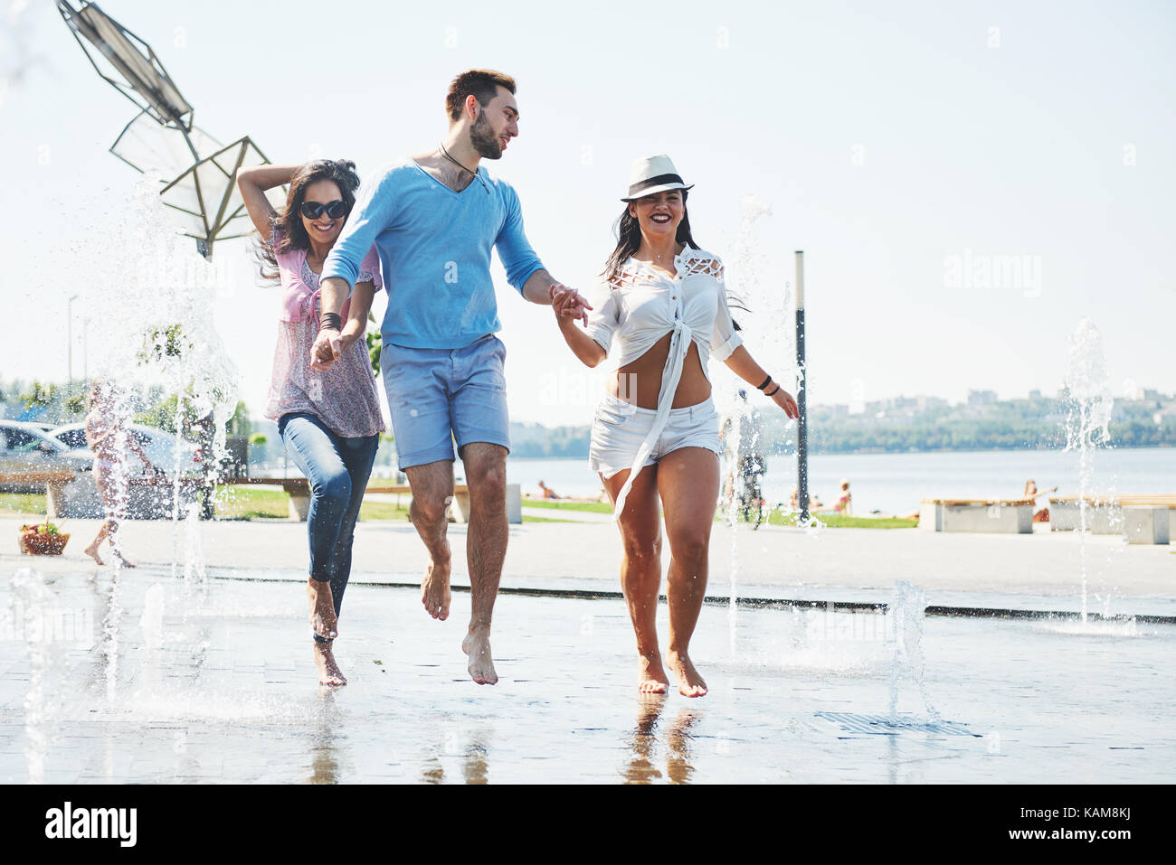Group of friends having fun next to the public fountain on summer day - Stock Image