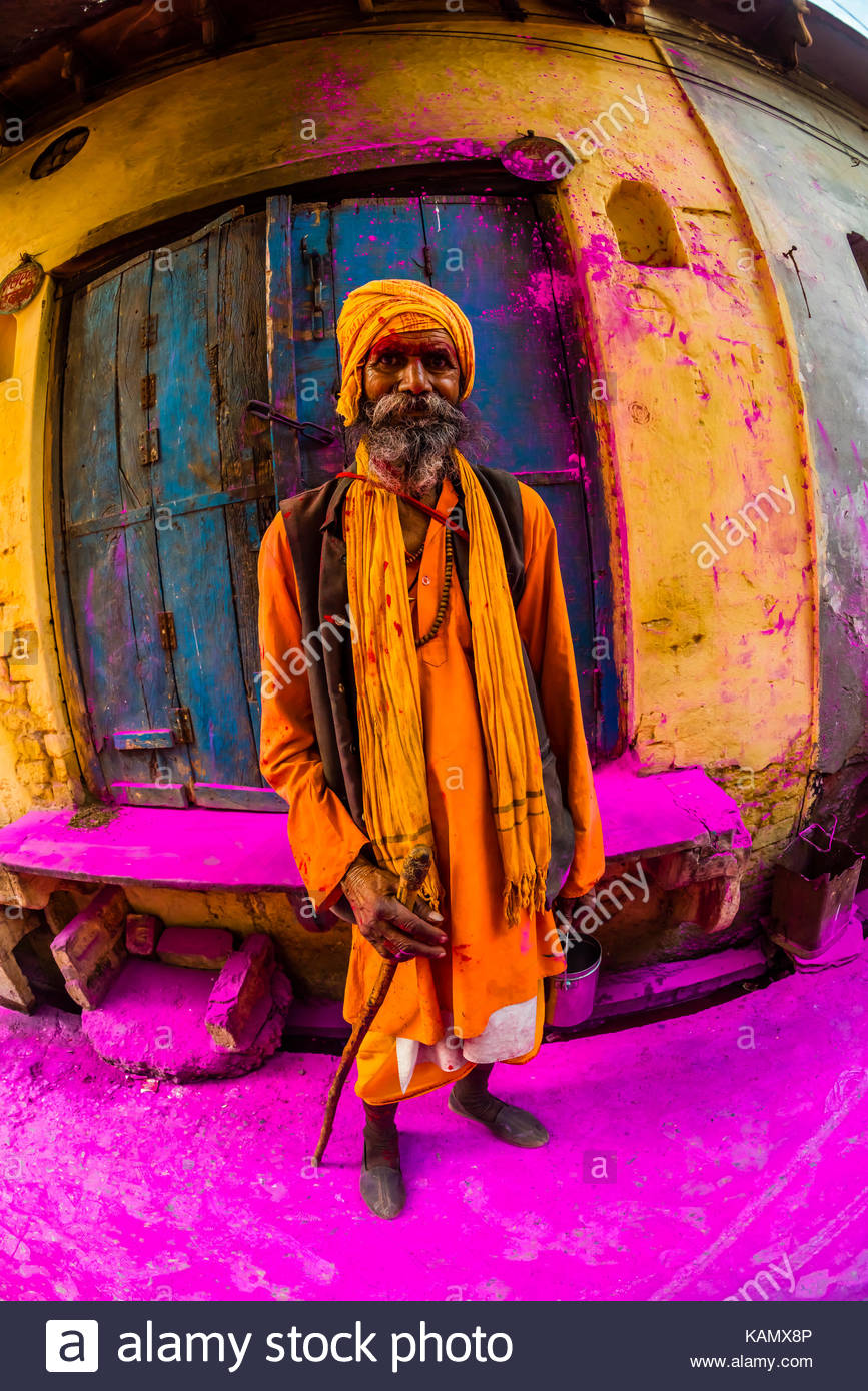 A saddhu (Holy man) walks down the street after a procession has passed throwing colored powders, Chhadi Mar Holi Stock Photo