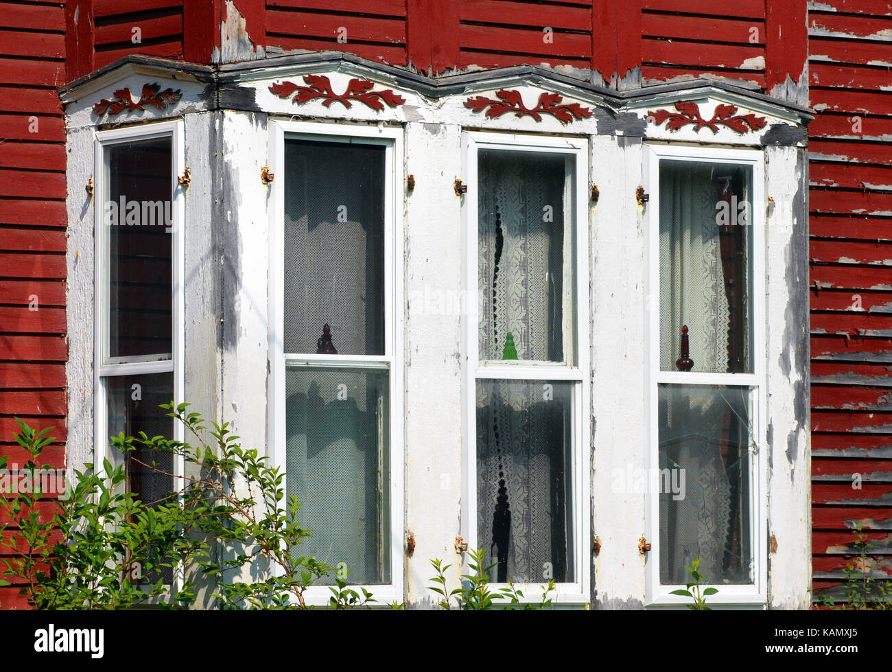 Aging Victorian home has red, peeling paint.  Matching, red wooden, leaves decorate window eaves. - Stock Image
