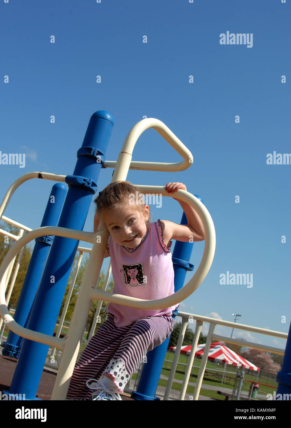 Little girl climbs through a metal hoop on playground equipment.  She is smiling and happy.  Equipment is blue and Stock Photo