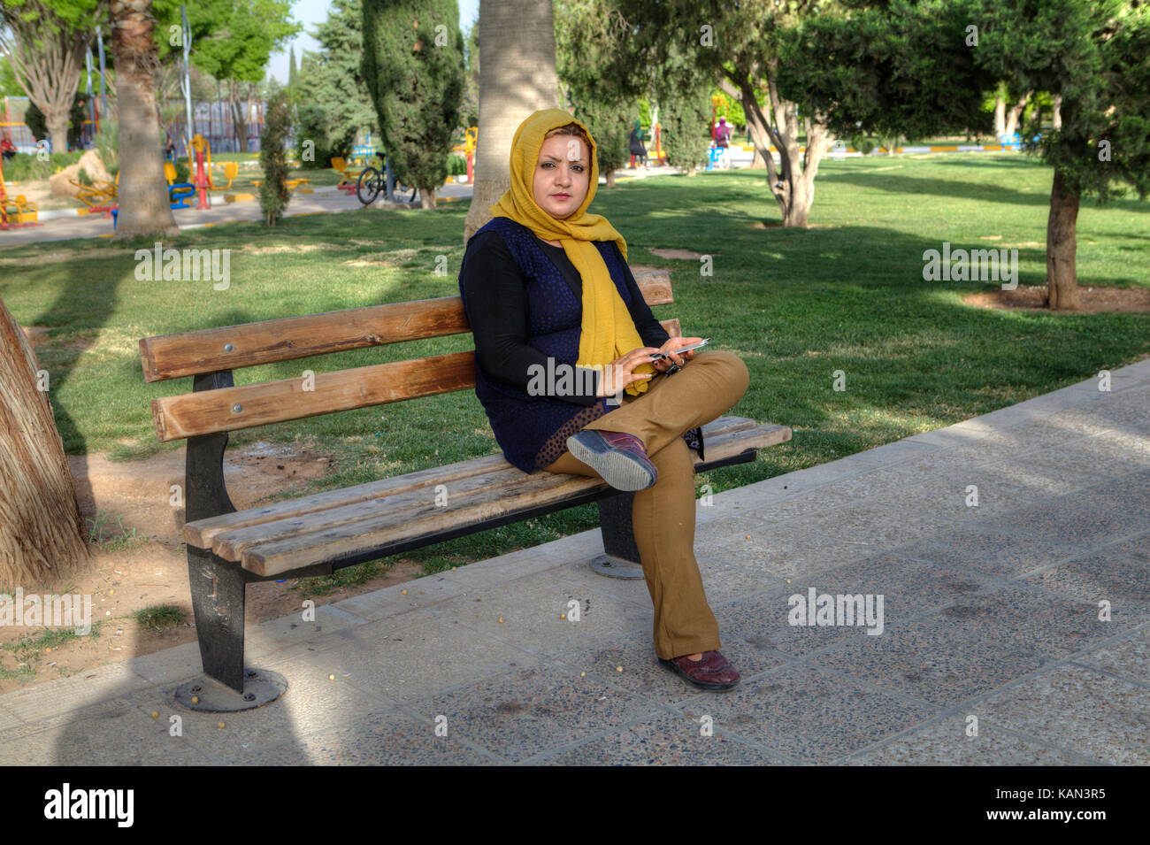 Fars Province, Shiraz, Iran - 19 april, 2017: Young Muslim woman in a yellow headscarf sitting alone on a park bench. - Stock Image
