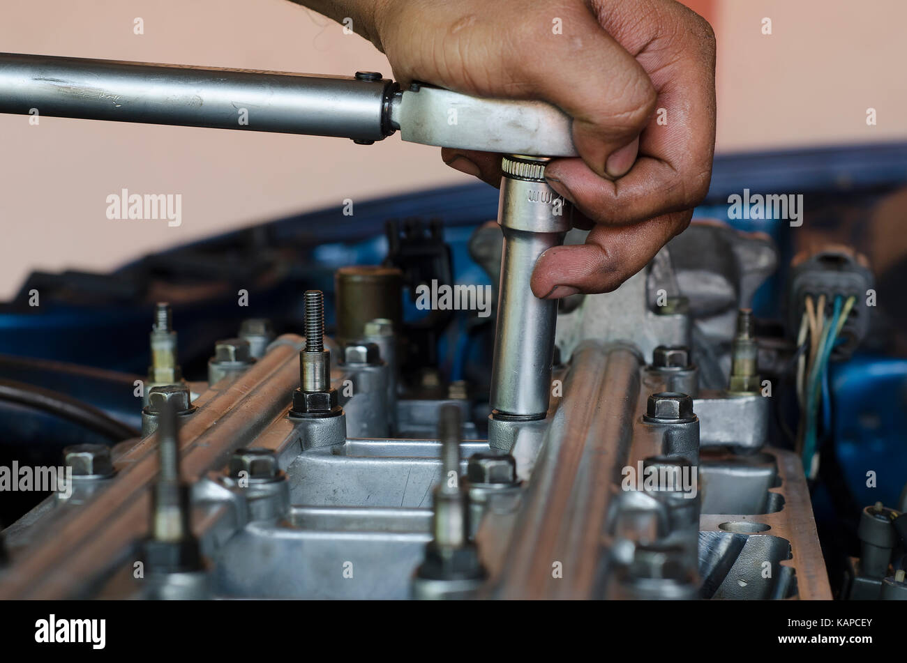 hand with torque wrench tightening screw car engine - Stock Image