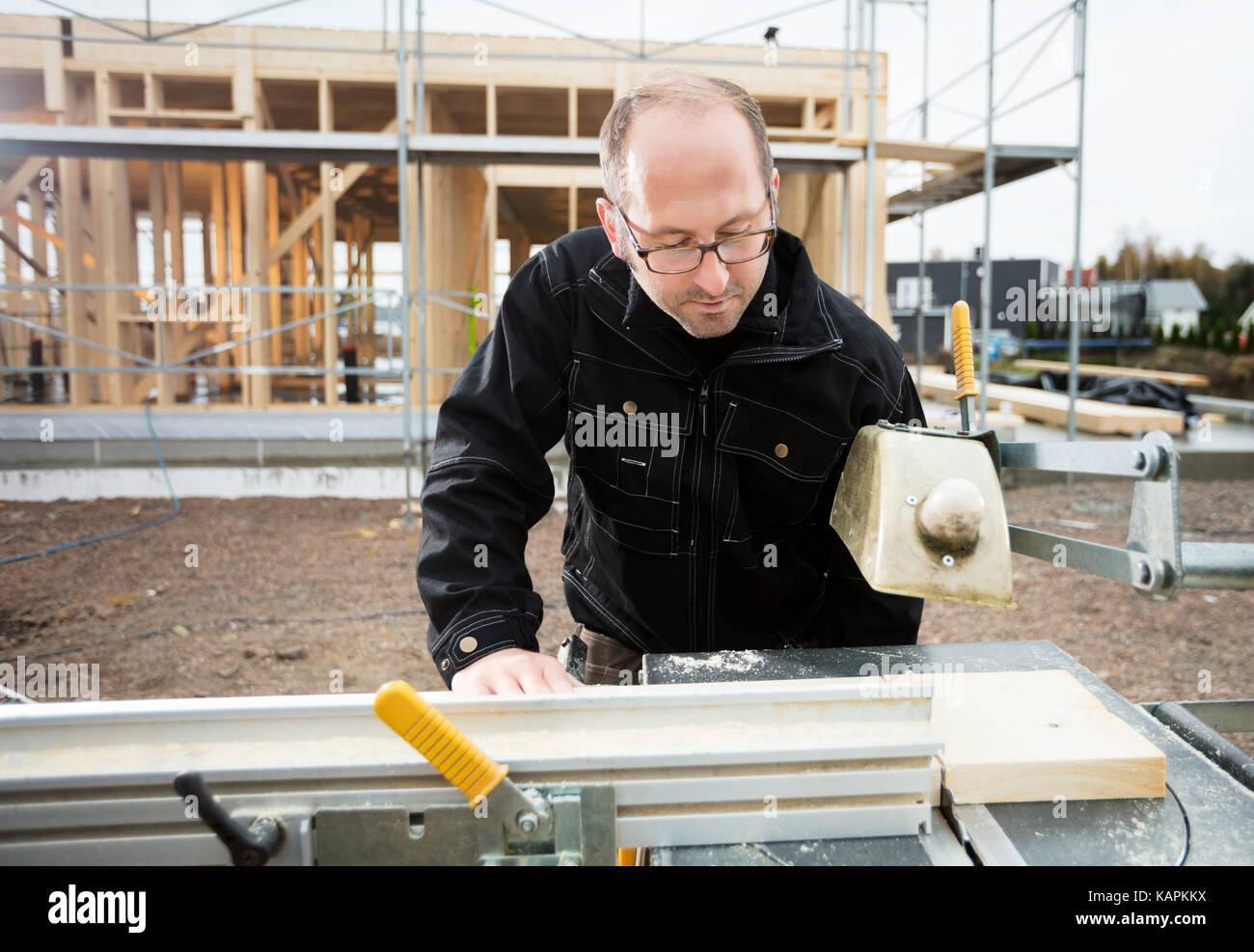 Carpenter Using Table Saw To Cut Plank At Site - Stock Image