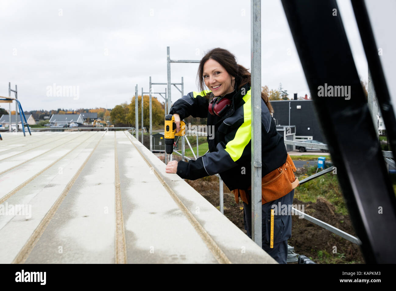 Female Carpenter Drilling Roof At Construction Site - Stock Image