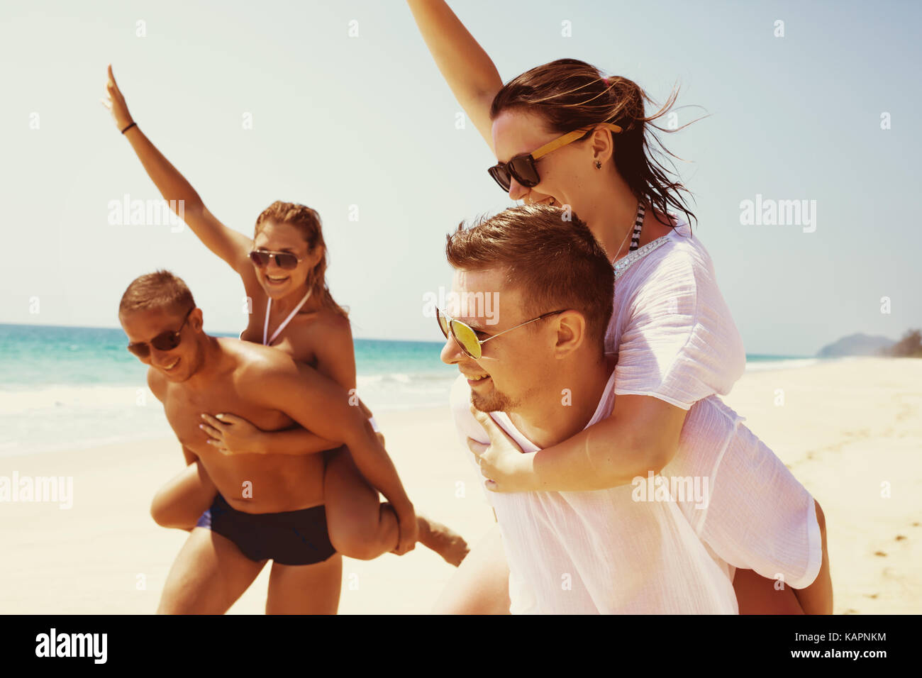 Two couples friends fun beach run - Stock Image