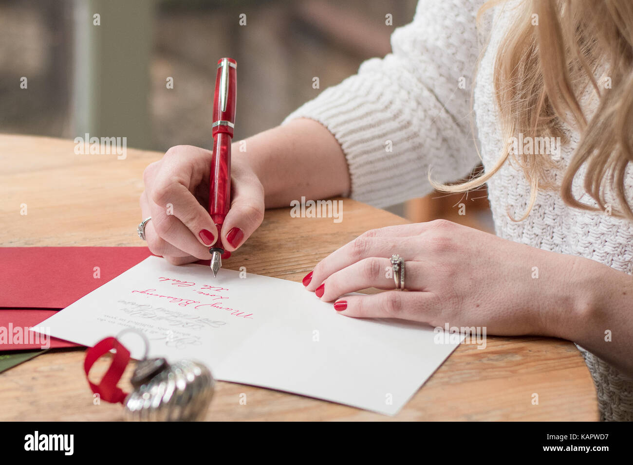 Young woman writing christmas cards with red nails a red pen and young woman writing christmas cards with red nails a red pen and holiday decorations on a wooden table publicscrutiny Gallery