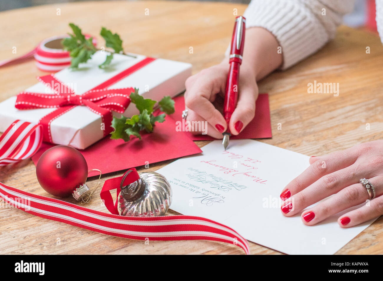 Young woman writing christmas cards with red nails a red pen and young woman writing christmas cards with red nails a red pen and holiday decorations on a wooden table m4hsunfo