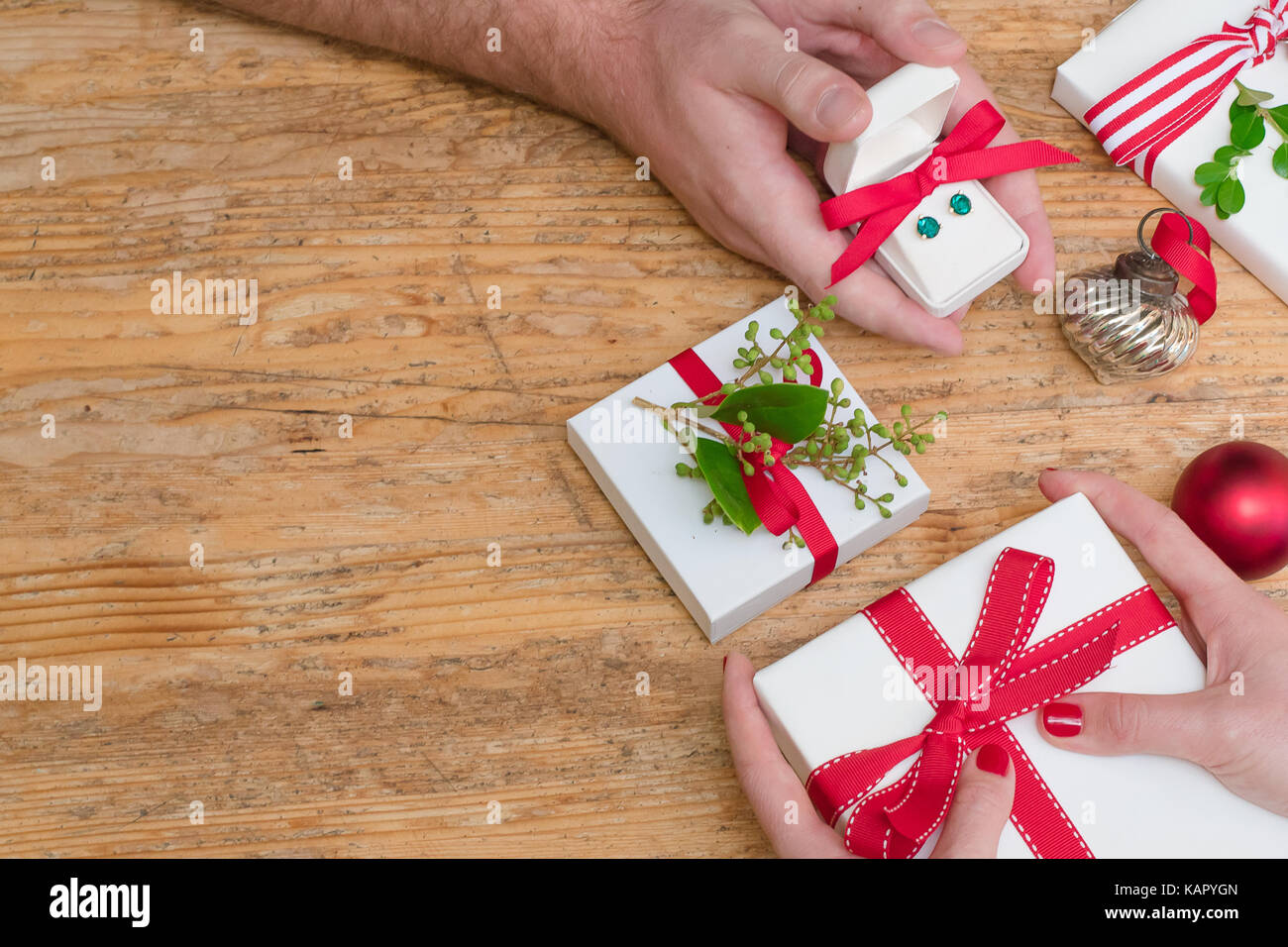 Romantic couple exchanges holiday Christmas gifts on a wooden table with Christmas decorations with room for copy Stock Photo