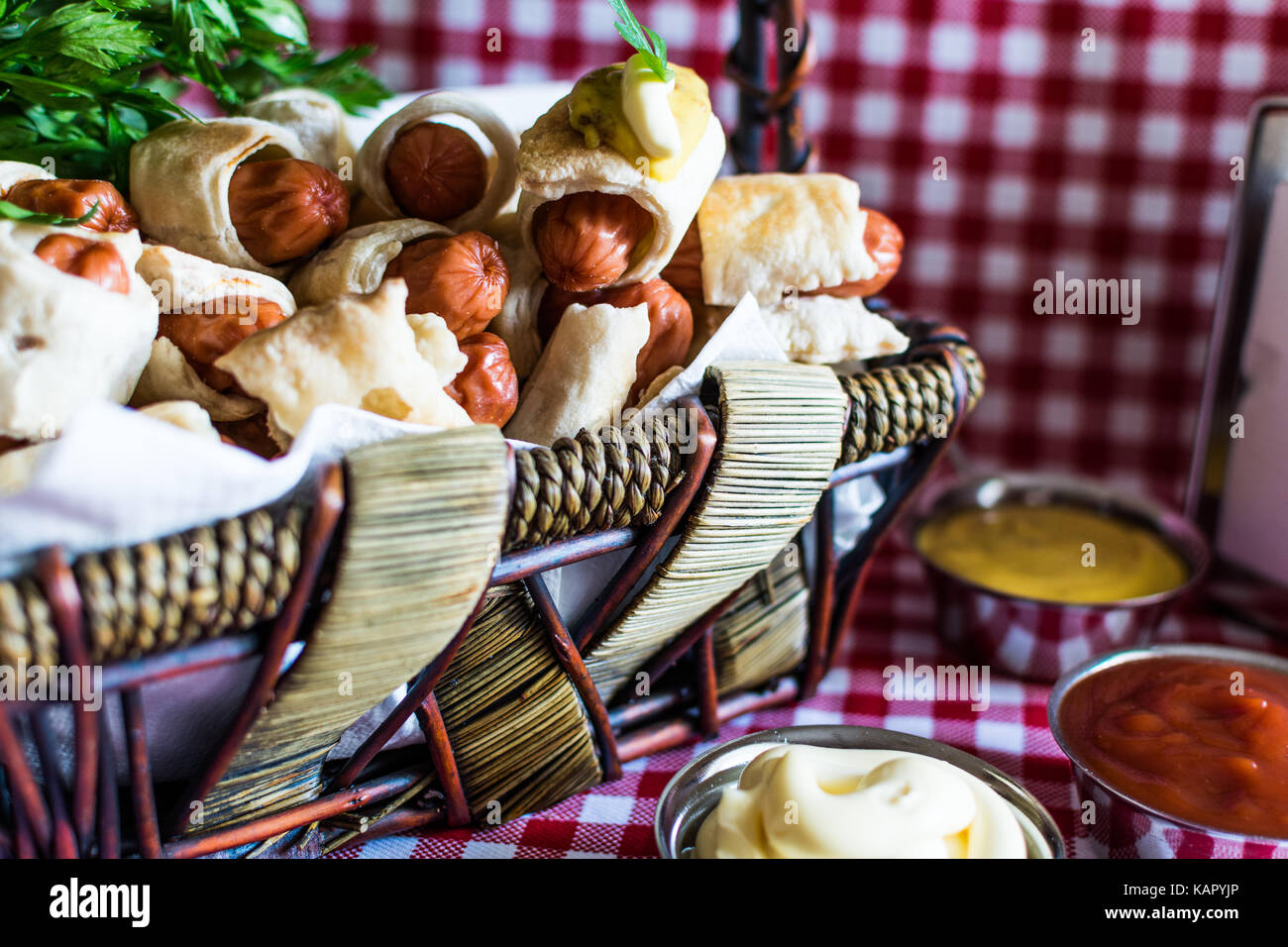 Wicker basket with artisan mini hot dogs (Sausage in the dough) with mustard, mayonnaise on a plaid background - Stock Image