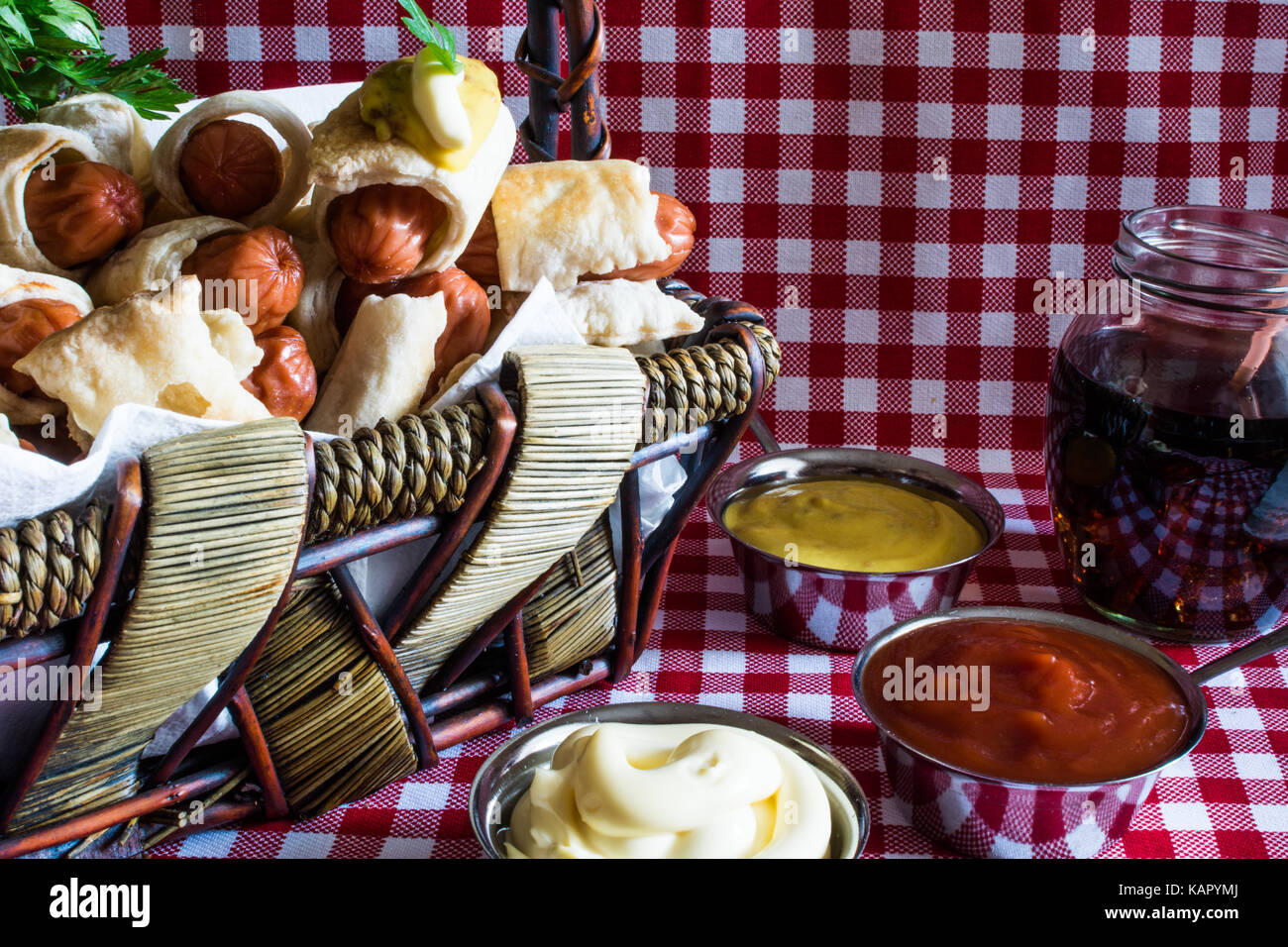 Wicker basket with mini artisan hot dogs (Sausage in the dough) with mustard, mayonnaise and cola on a plaid background - Stock Image