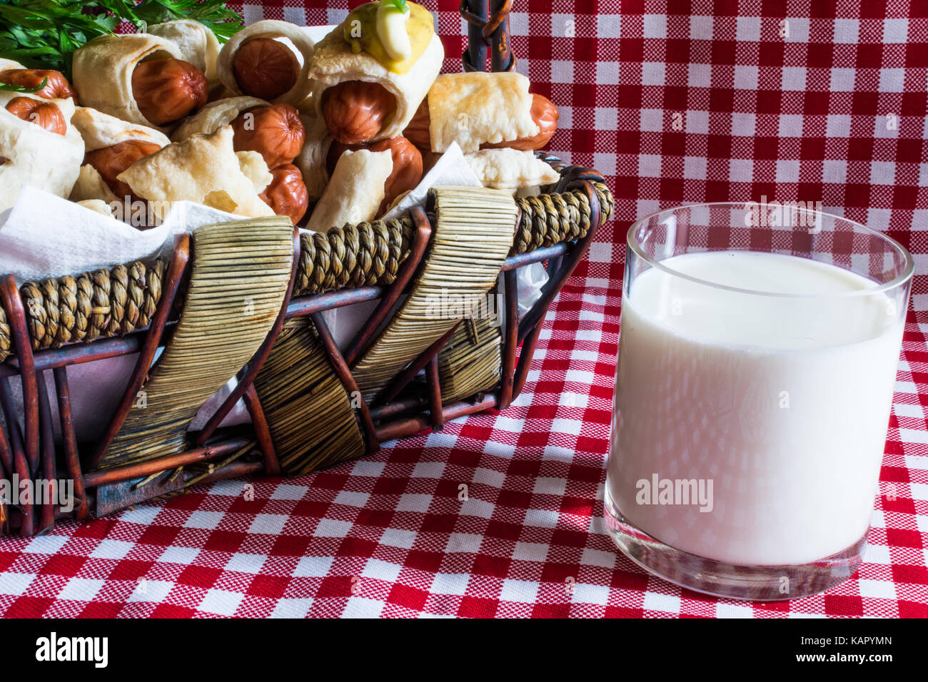 Wicker basket with mini artisan hot dogs (Sausage in the dough) and a glass of fresh cow's milk of the village, - Stock Image