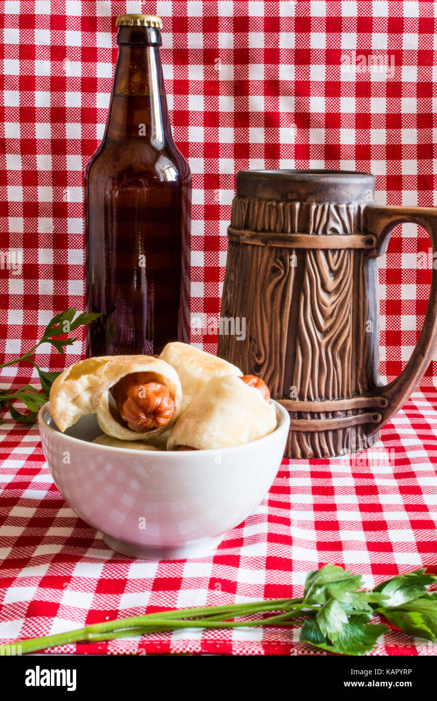 Plate Mini hot dogs homemade (sausage in pastry) on napkin with a bottle of dark beer and earthenware mug on a plaid - Stock Image