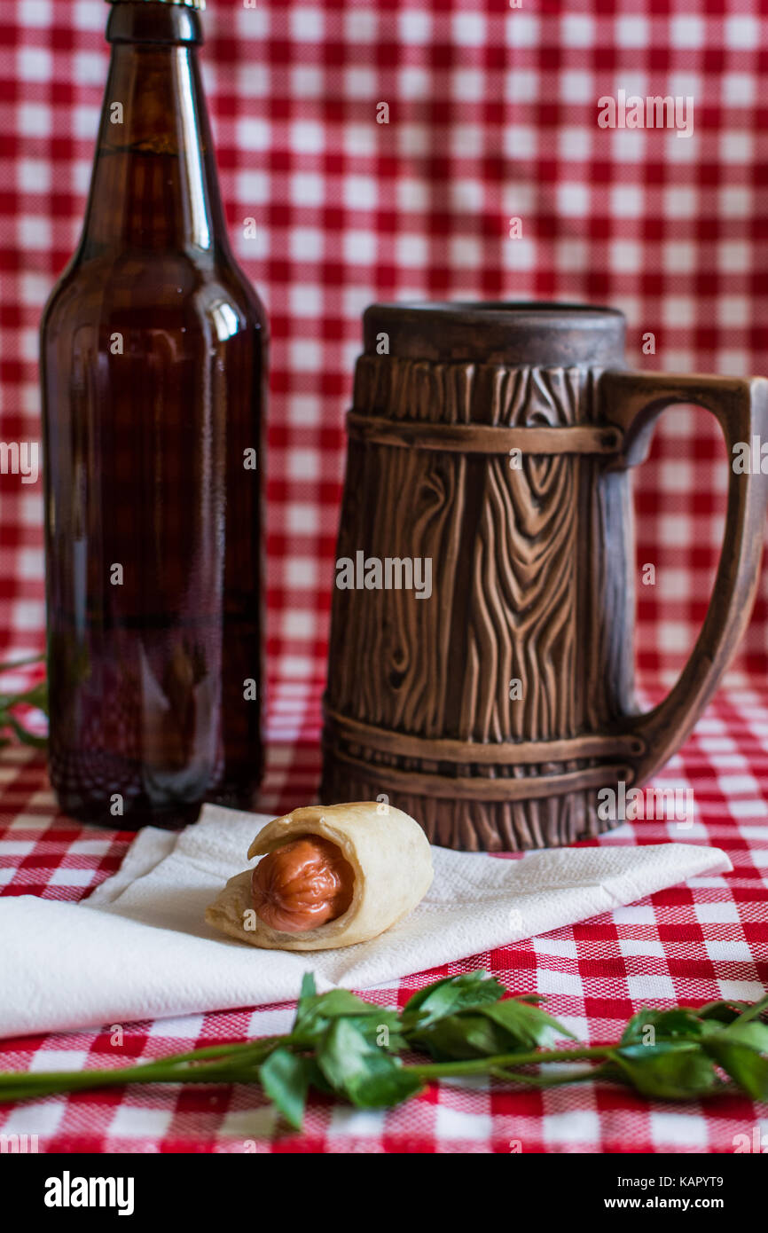 Homemade Mini hot dog (sausage in pastry) on napkin with a bottle of dark beer and earthenware mug on a plaid background - Stock Image