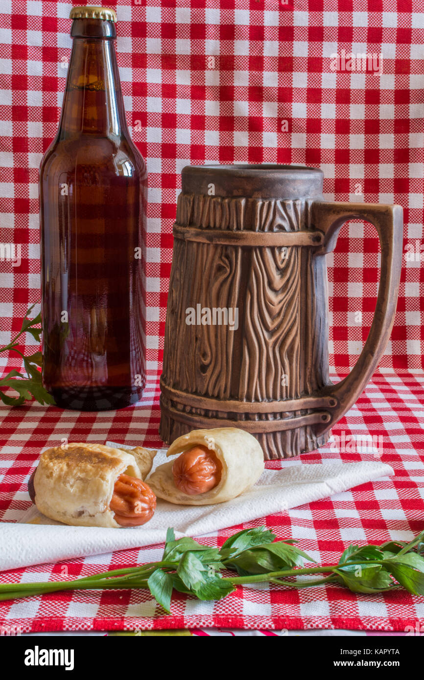Homemade Mini hot dogs (sausage in pastry) on napkin with a bottle of dark beer and earthenware mug on a plaid background - Stock Image