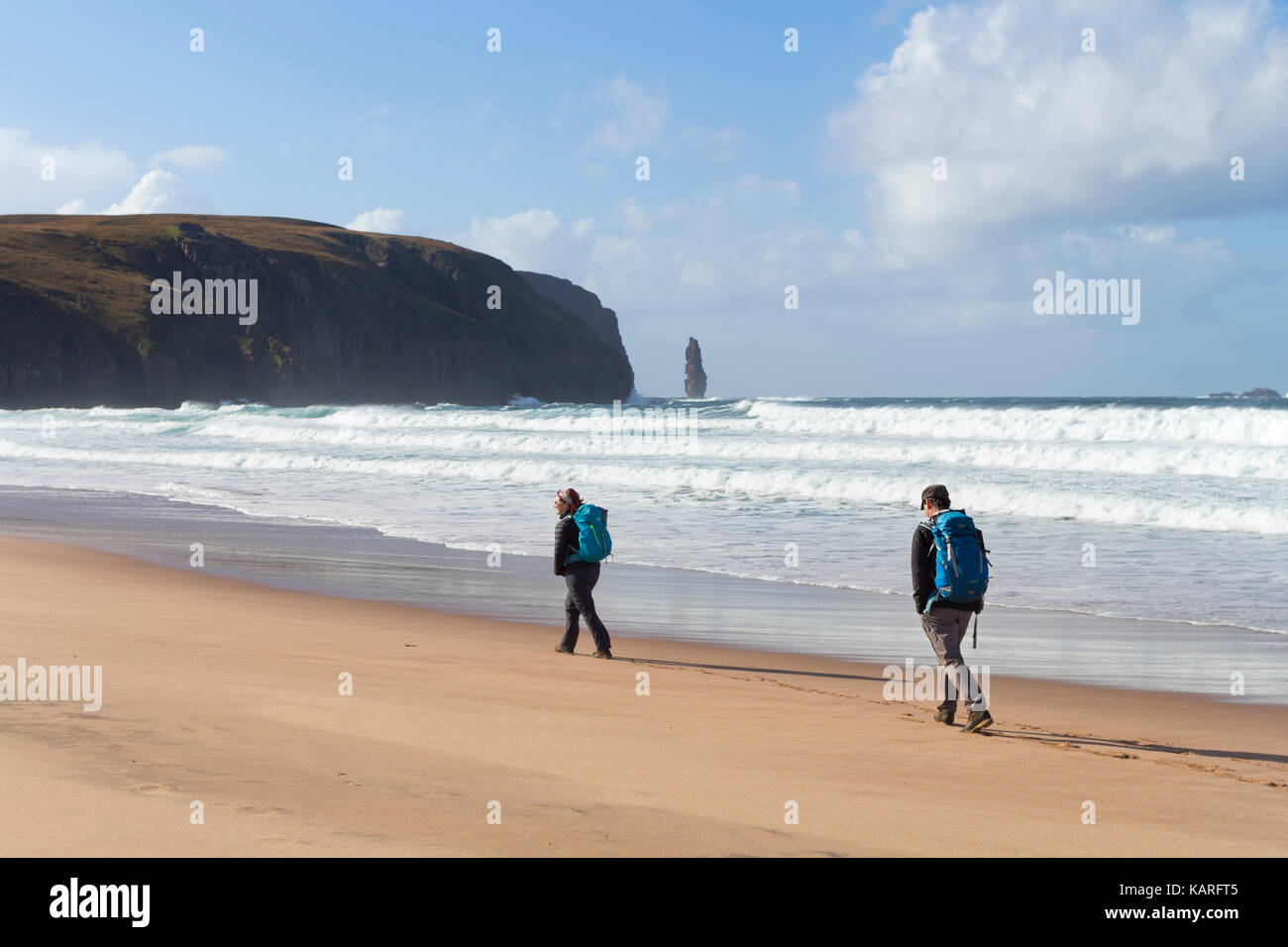 Two People Walking Along the Coast at Sandwood Bay with the Sea Stack of Am Buachaille in the Distance, Sutherland, - Stock Image