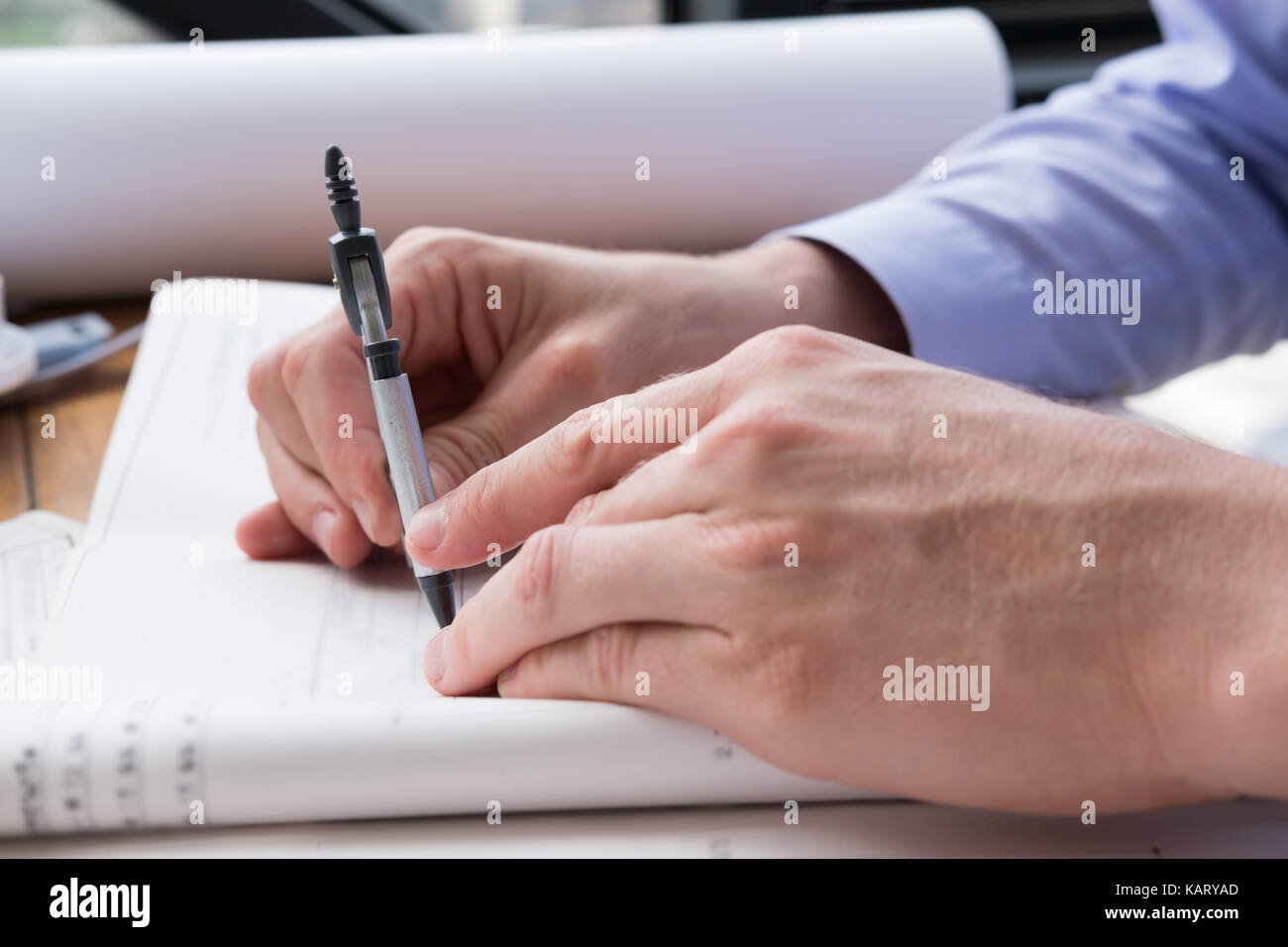 Architect hand holding drawing compass working on construction plan architect hand holding drawing compass working on construction plan at office engineer inspect blueprint with divider at workplace young man sketchi malvernweather Image collections