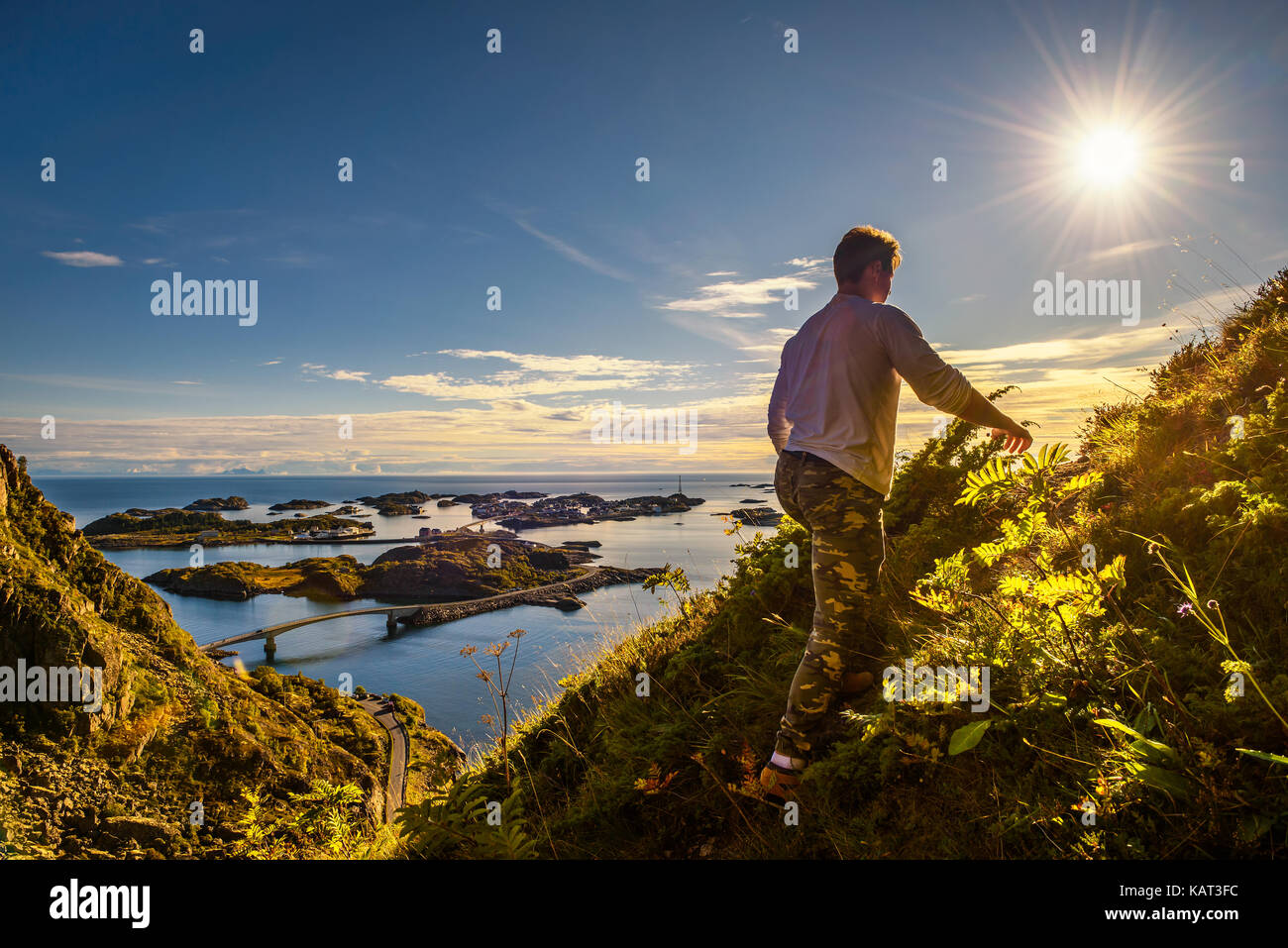 Male hiker going to the top of mount Festvagtinden with views over the village of Henningsvaer on Lofoten islands in Norway Stock Photo