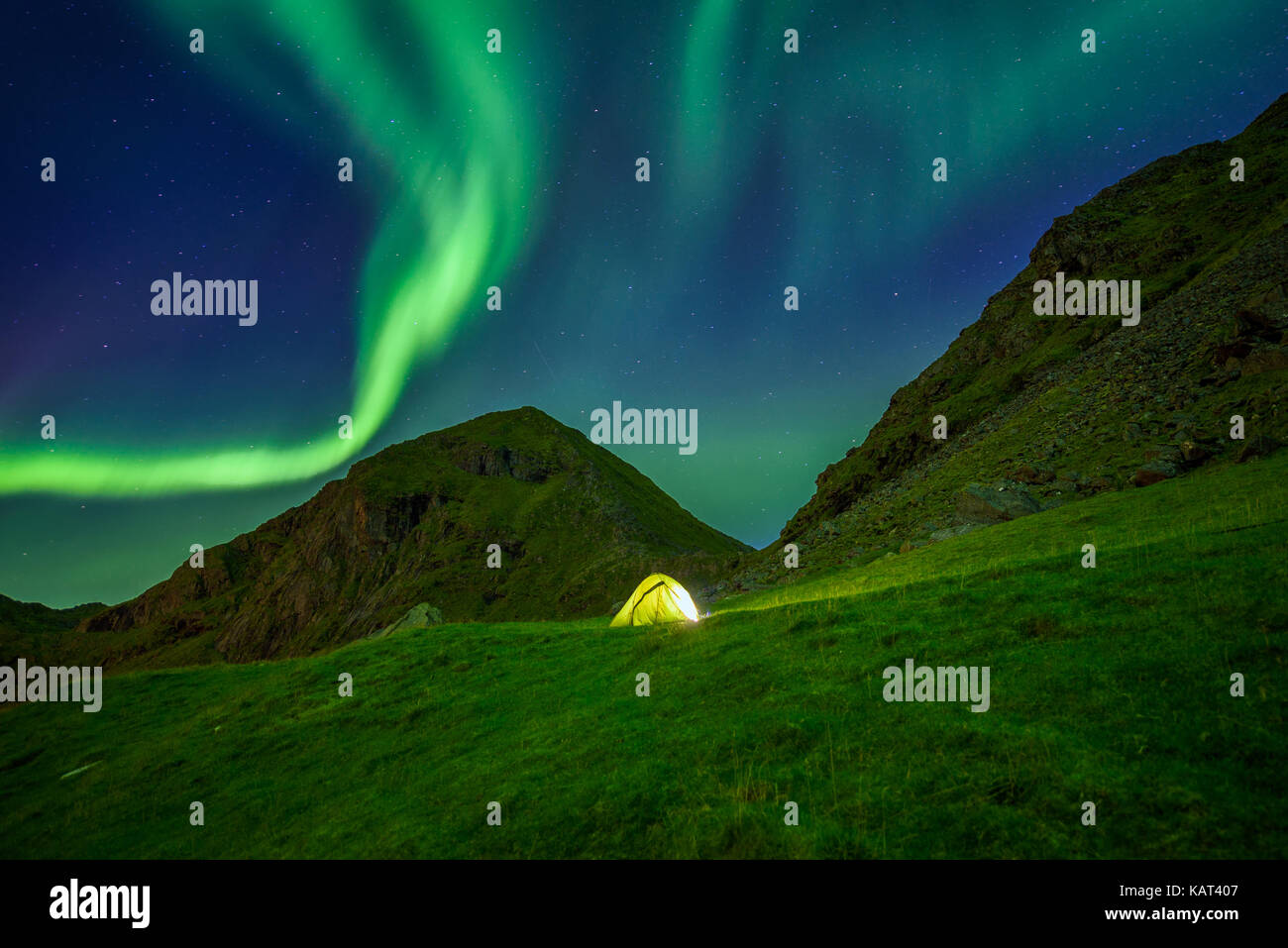 Illuminated tent in the Lofoten islands in Norway with the northern lights overhead (Aurora Borealis) - Stock Image