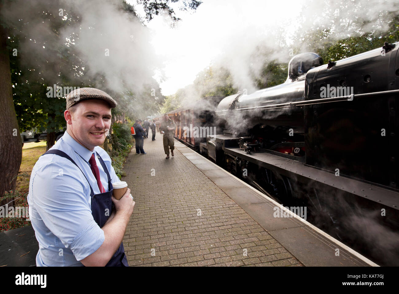 North Norfolk Railway engineer takes a break at Holt sation on the Poppy Line during a 1940s festival. - Stock Image