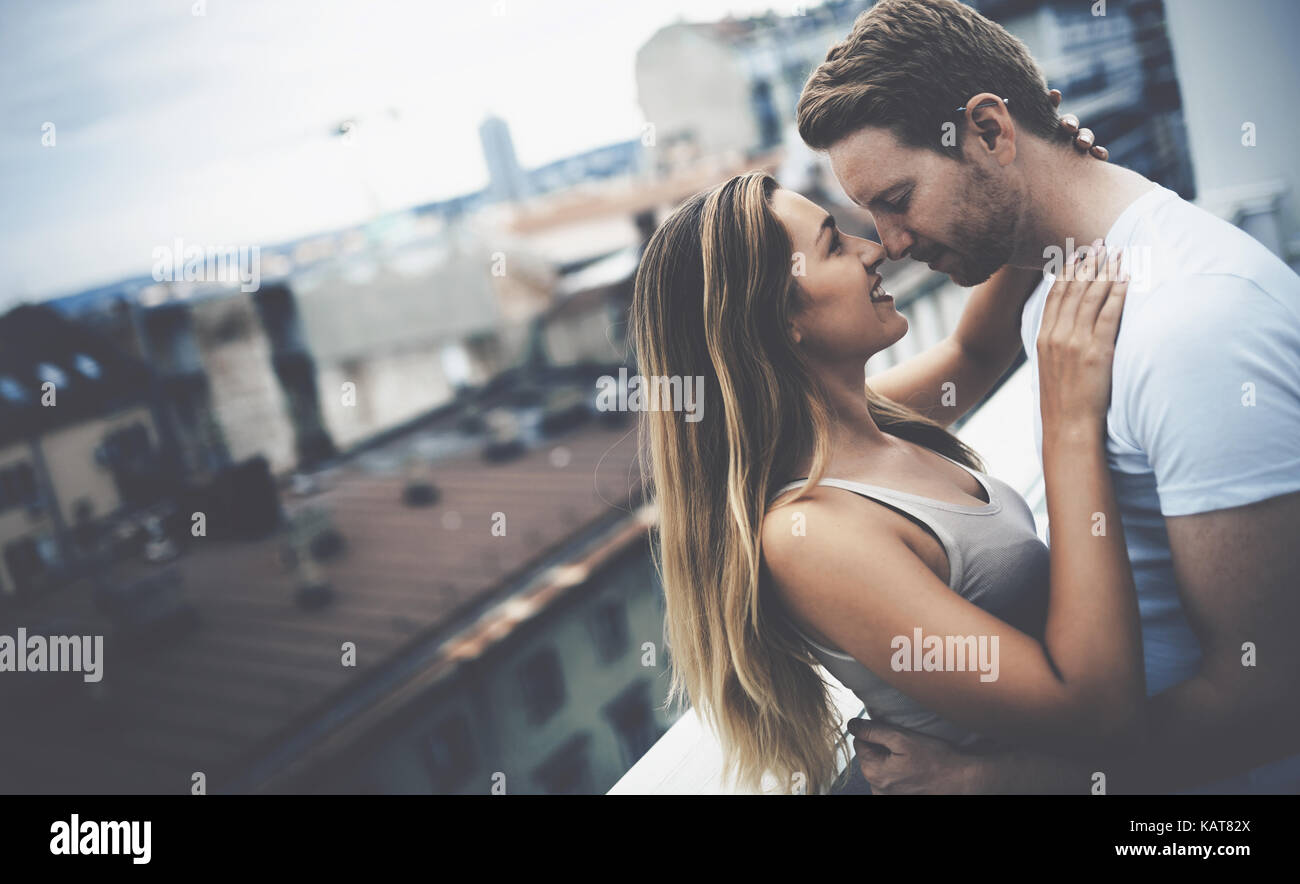 Romantic couple kissing on rooftop - Stock Image