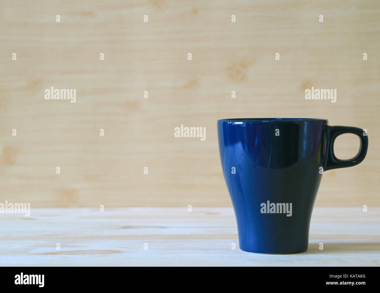 Front view of navy blue mug on the light color wooden table - Stock Image