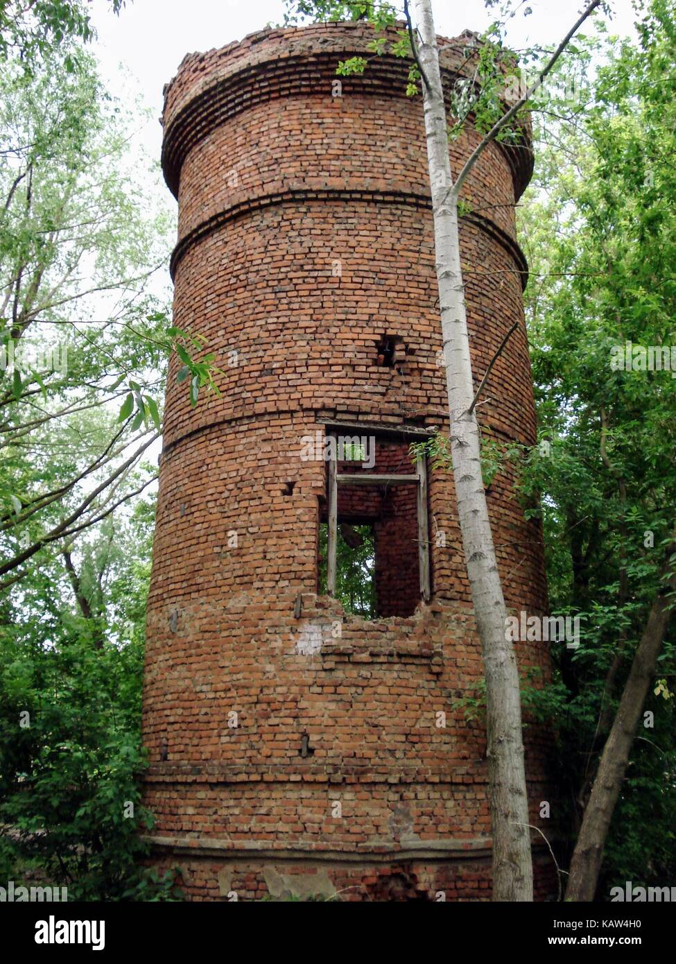 Destroyed water tower of red brick in Russia. She is about 120 years old - it was built before the revolution. - Stock Image