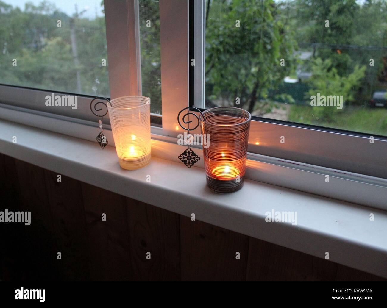 Two candles burning on the windowsill in deep candle holders. - Stock Image