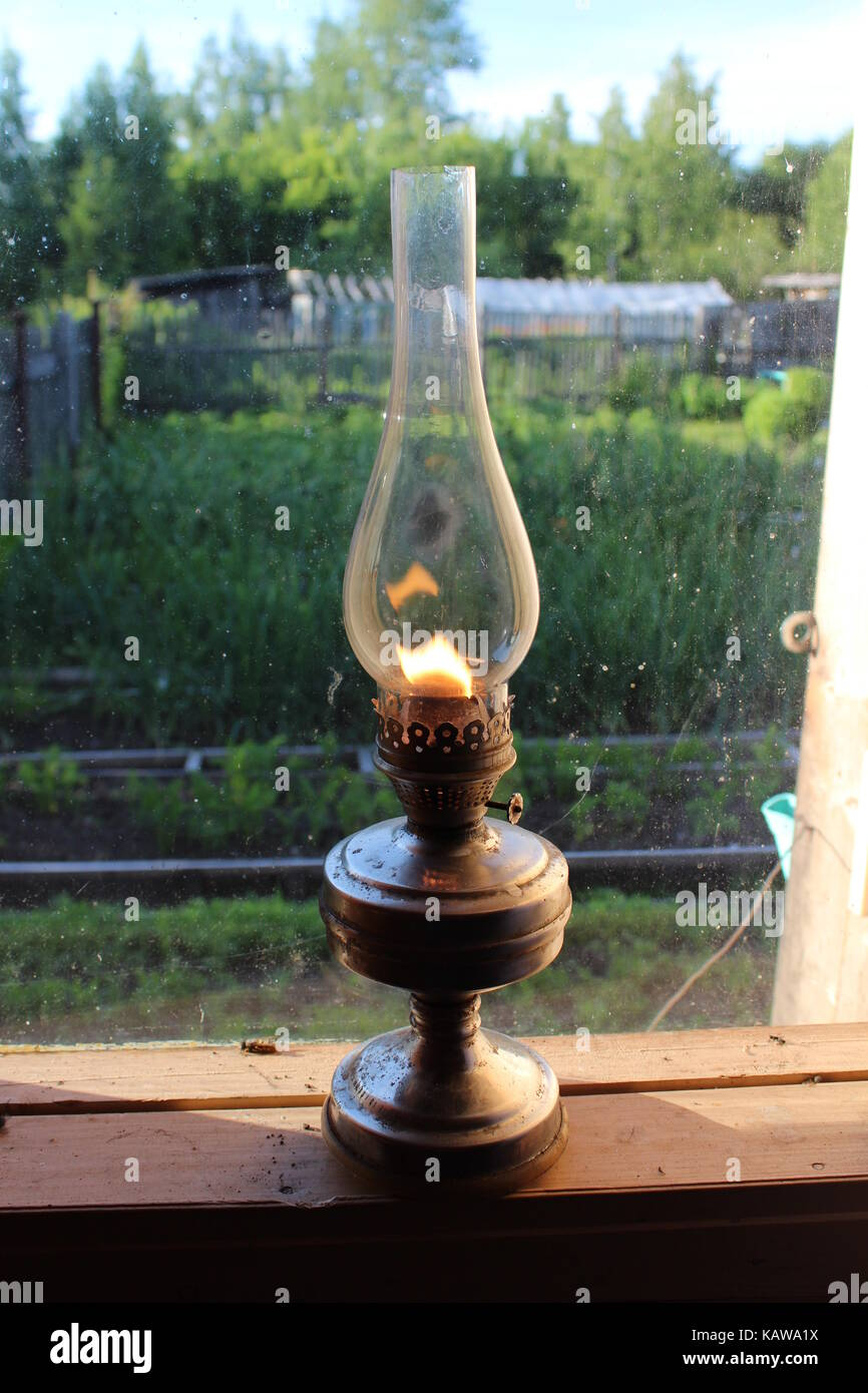 An old-fashioned kerosene lamp stands on a wooden window-sill. Stock Photo