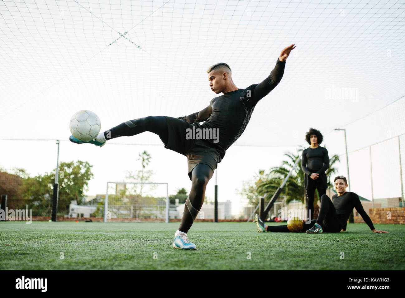Soccer player kicking ball. Young footballer practicing on football field. - Stock Image